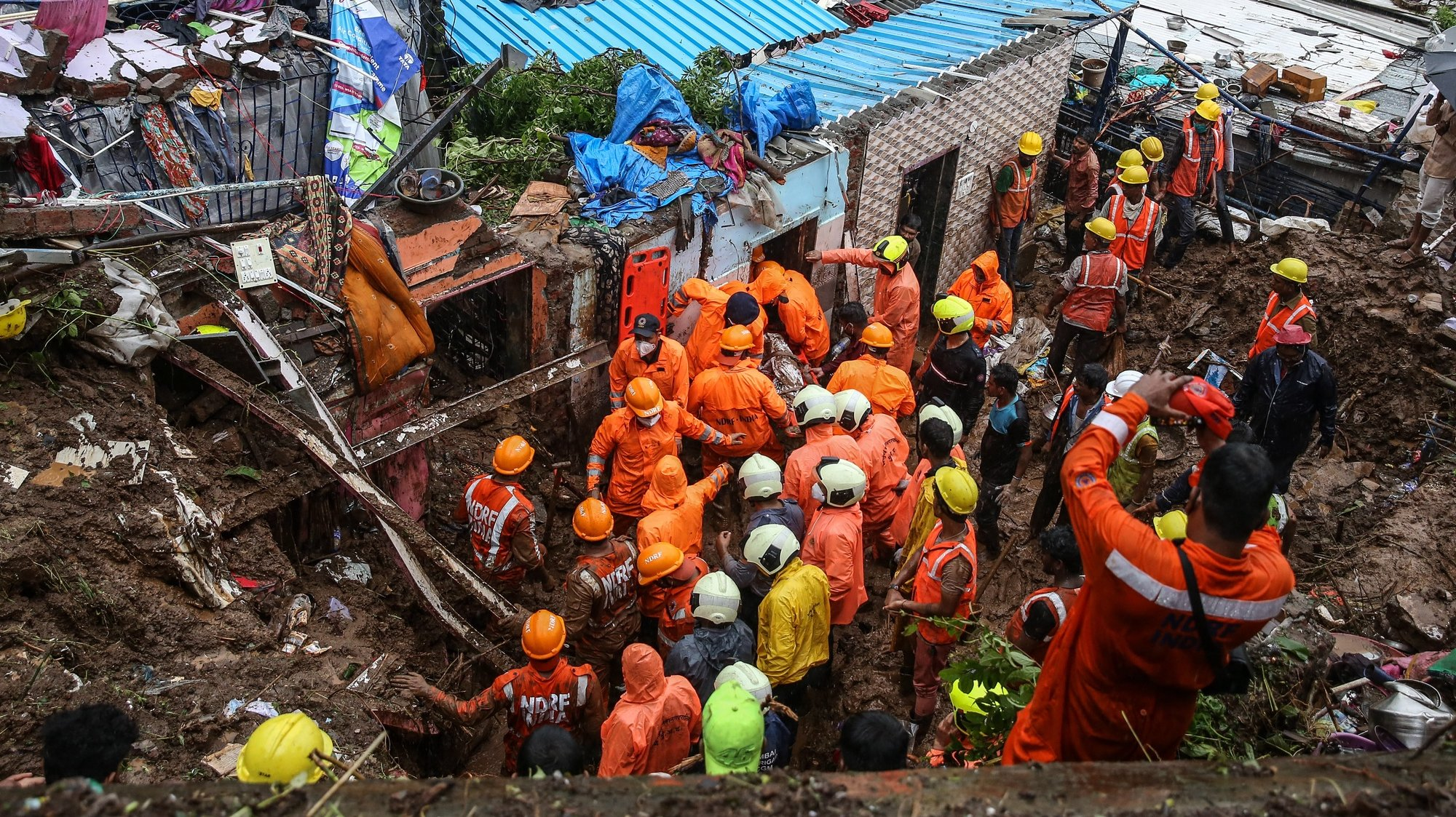 epa09352181 National Disaster Response Force (NDRF) personnel recover dead body from the rubble during a rescue operation in the aftermath of a landslide at a Bharat Nagar slum in Chembur, Mumbai, India, 18 July 2021. According to the police and municipal officials at least 22 people are dead and several others injured after a wall collapsed on some shanties in Chembur's Bharat Nagar area due to a landslide after heavy rainfall in the city.  EPA/DIVYAKANT SOLANKI