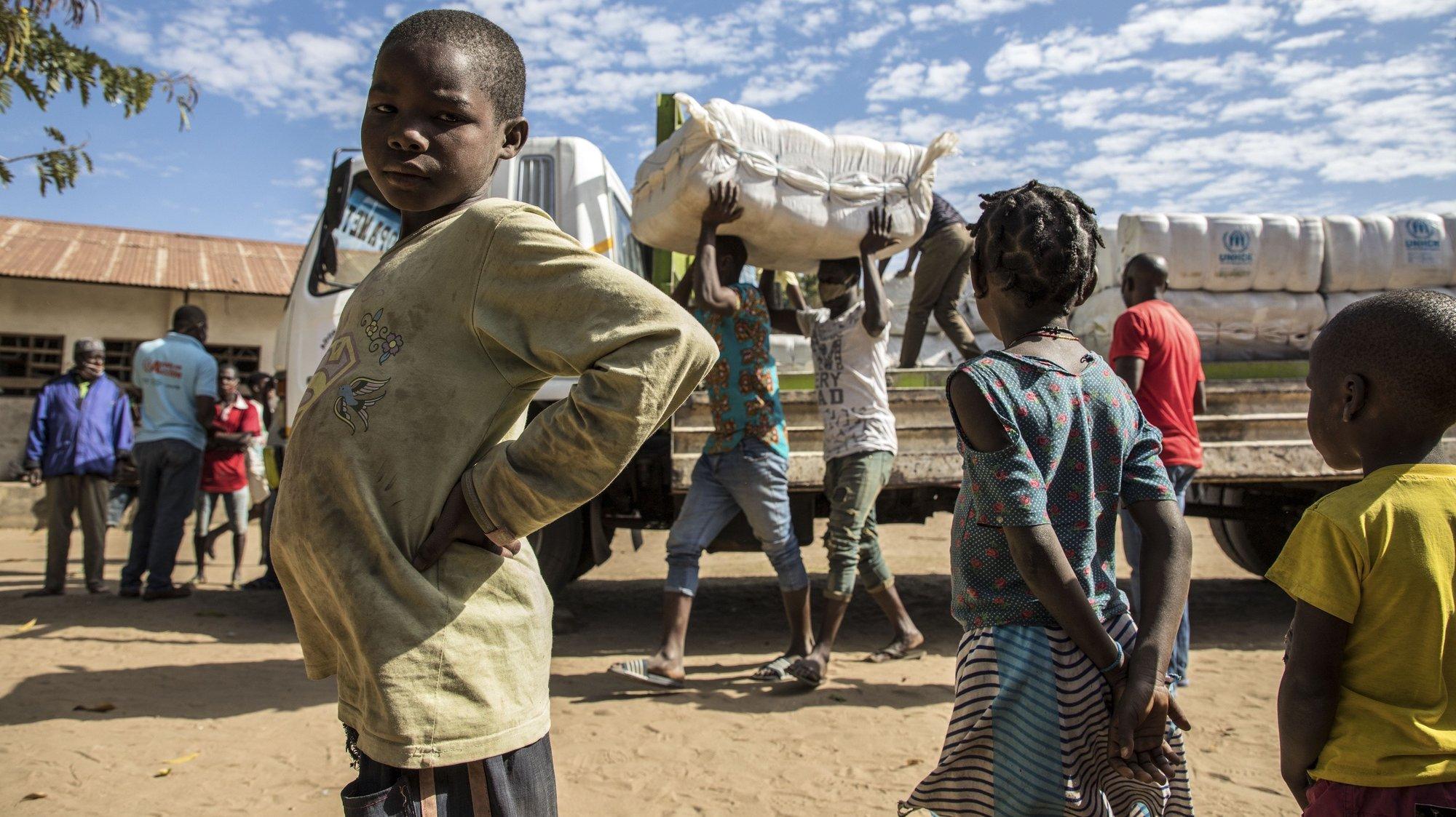 """Deslocados da violência armada em Cabo Delgado durante a distribuição de mantas no campo de deslocados de Manono, Metuge, Moçambique 22 de julho de 2020. """"Não é impossível"""" cumprir as medidas nestes campos, diz Daniel Timme, chefe de comunicação do Fundo das Nações Unidas para a Infância (UNICEF), """"mas é um processo educacional"""". (ACOMPANHA TEXTO DE 26 DE JULHO DE 2020). RICARDO FRANCO/LUSA"""