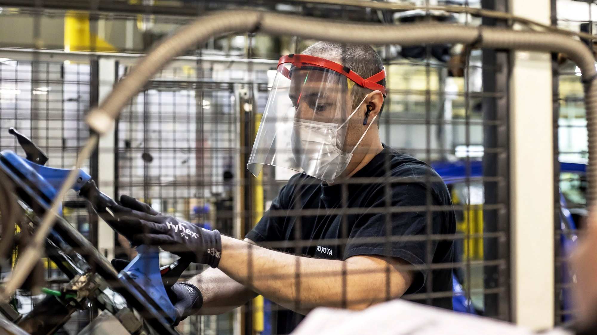 epa08389681 A Toyota employee wears a protective face shield while working at the car manufacturing plant where the Yaris model is assembled for the European market in Onnaing, near Valenciennes, northern France, 28 April 2020. Toyota is the first vehicle plant reopening in France since the start of the national lockdown due the ongoing coronavirus COVID-19 pandemic. Only one third of the employees returned to work, having to respect strong safety measures. The challenge is to learn how to work differently from now on. The workers' temperature is checked upon arrival and they have to wear a mask which they should change twice a day.  EPA/SEBASTIEN COURDJI