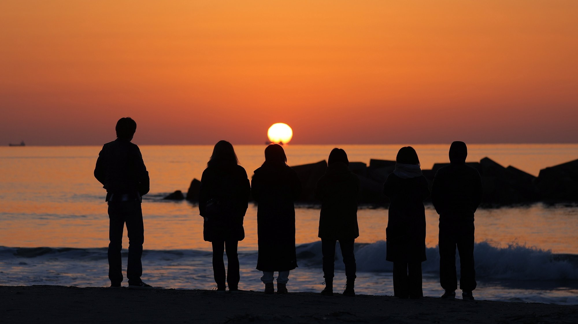 epa09066731 Local residents stand on the seashore at sunrise in Arahama, Miyagi prefecture, northeastern Japan, early 11 March 2021. Japan is commemorating the 10th anniversary of the Great East Japan Earthquake and subsequent tsunami in which approximately 20,000 people lost their lives on 11 March 2011.  EPA/JIJI PRESS JAPAN OUT EDITORIAL USE ONLY/  NO ARCHIVES