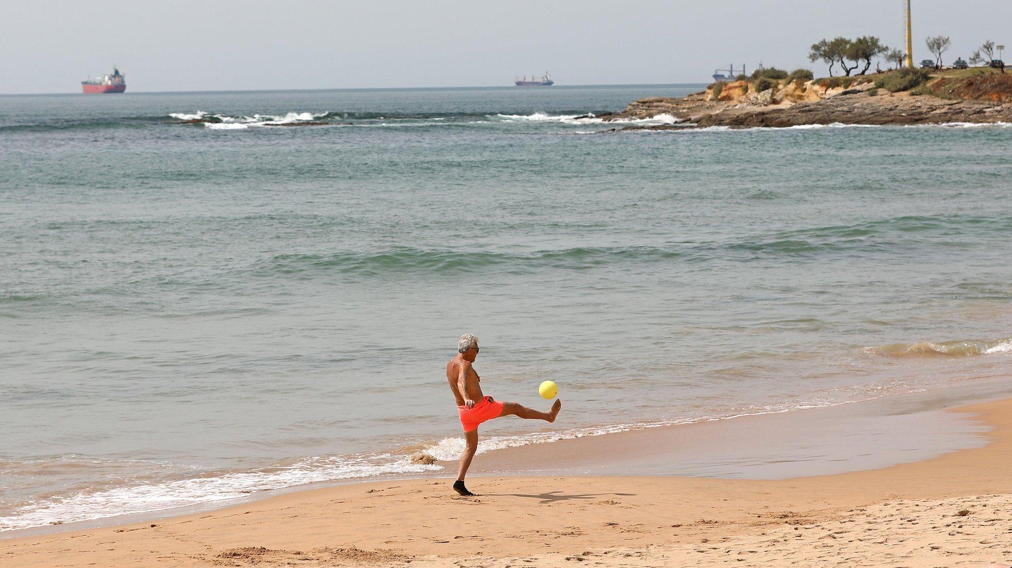 Um homem joga à bola na praia de Carcavelos durante o confinamento que se prolonga até ao dia 05 de abril, no âmbito das medidas de contenção da pandemia de covid-19, em Cascais, 27 de Março de 2021. A circulação entre concelhos em Portugal continental está proibida desde as 00:00 de ontem e as 05:00 de 05 de abril, no âmbito do estado de emergência para combater a pandemia de covid-19. ANTÓNIO PEDRO SANTOS/LUSA