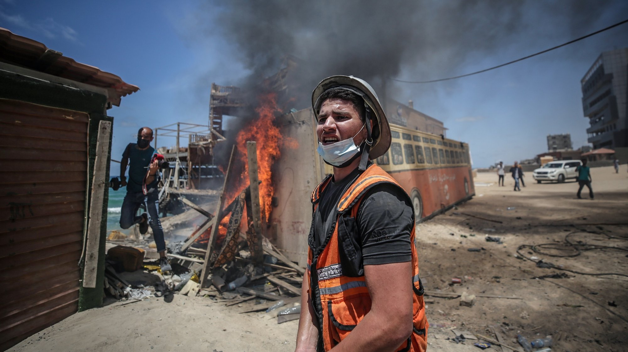 epa09206953 A Palestinian Civil Defense man works at the site of Israeli strikes in Gaza City, 17 May 2021. Three Palestinians were reportedly killed after Israeli air strikes. In response to days of violent confrontations between Israeli security forces and Palestinians in Jerusalem, various Palestinian militant factions in Gaza launched rocket attacks since 10 May that killed at least ten Israelis to date. According to the Palestinian Ministry of Health, at least 198 Palestinians, including 58 children, were killed in the recent retaliatory Israeli airstrikes.  EPA/MOHAMMED SABER