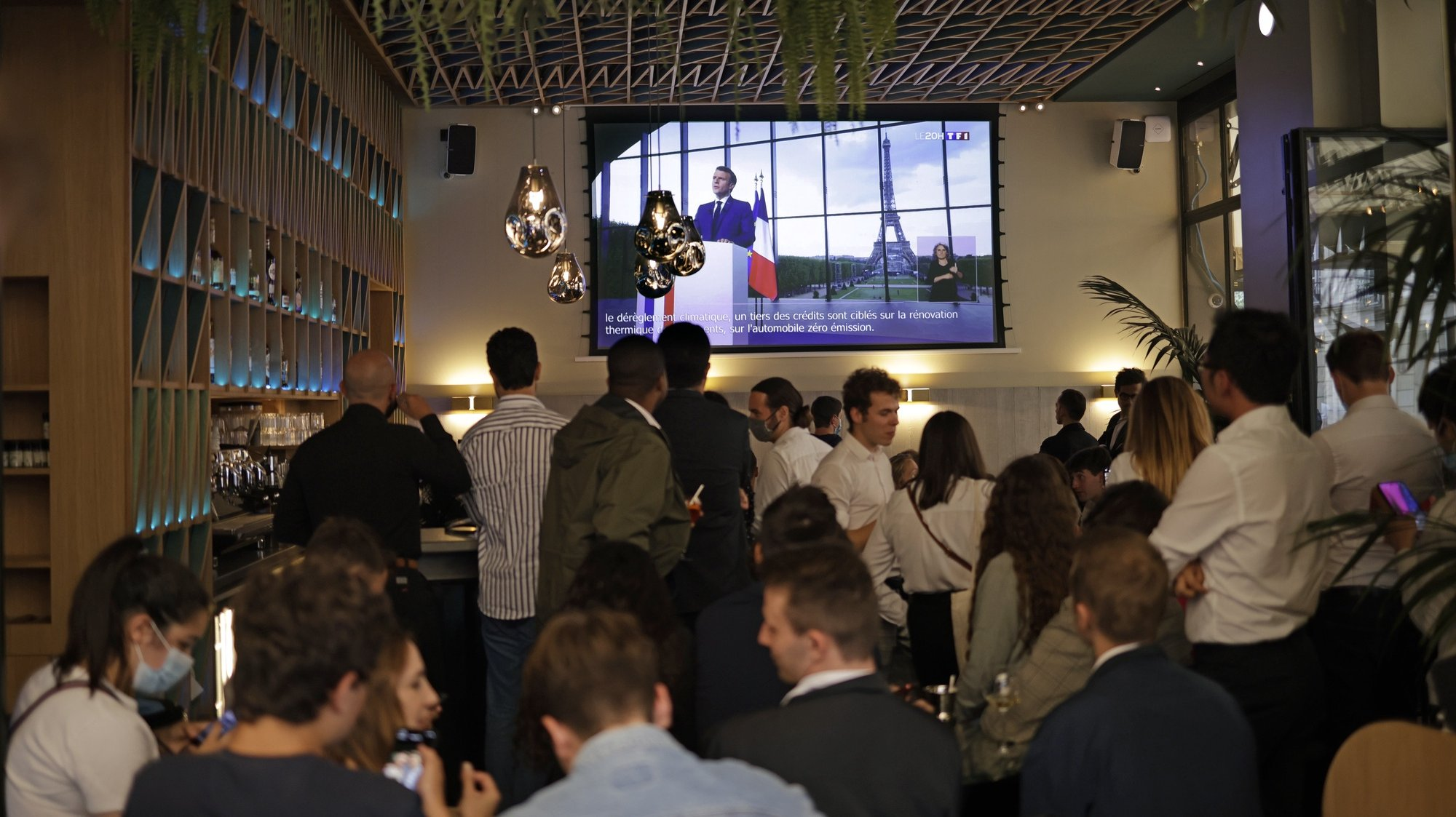 epa09340935 Bar customers watch French President Emmanuel Macron making a televised address to the nation to announce enhanced measures to fight the spread of Covid19 coronavirus, as France faces a possible resurgence of the pandemic, in Paris, France, 12 July 2021.  EPA/YOAN VALAT