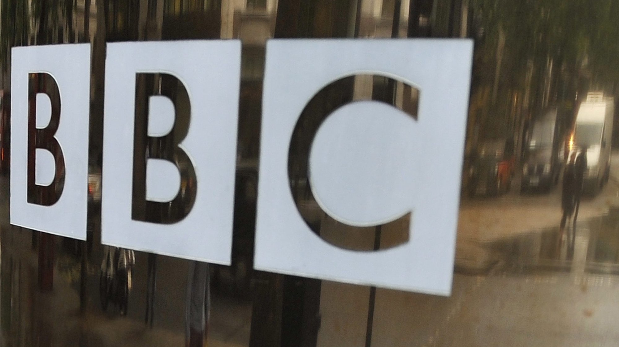 epa03425893 (FILES) A file photo showing the BBC's well known logo on the glass doors of one of their studios in central London 22 June 2011. The broadcasting corporation's director general George Entwhistle said, in the light of abuse allegations against the late Sir Jimmy Saville, a veteran dj and presenter with BBC,  all 'outstanding questions' would be addressed, but only after ' police had finished everything they have to do'  EPA/ANDY RAIN *** Local Caption *** 02789635