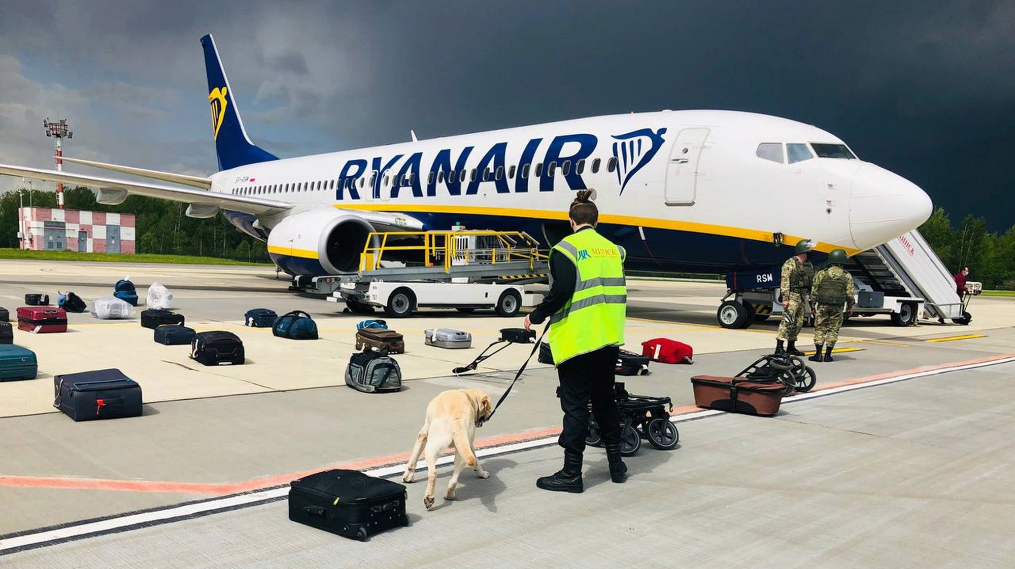 epa09224989 A handout photo made available by ONLINER.BY shows security with a sniffer dog checking the luggage of passengers in front of Ryanair Boeing 737-8AS (flight FR4978), carrying opposition figure Roman Protasevich, in Minsk, Belarus, 23 May 2021 (issued 24 May 2021). A Ryanair flight from Athens, Greece to Vilnius, Lithuania, with Belarus' opposition journalist Roman Protasevich onboard, was diverted and forced to land in Minsk on 23 May 2021, after an alleged bomb threat. Protasevich was detained by Belarusian Police after landing, as Belarusian Human Rights Center 'Viasna' reports, Lithuanian President Gitanas Nauseda demanded the immediate release of Protasevich.  EPA/ONLINER.BY HANDOUT -- BEST QUALITY AVAILABLE -- HANDOUT EDITORIAL USE ONLY/NO SALES