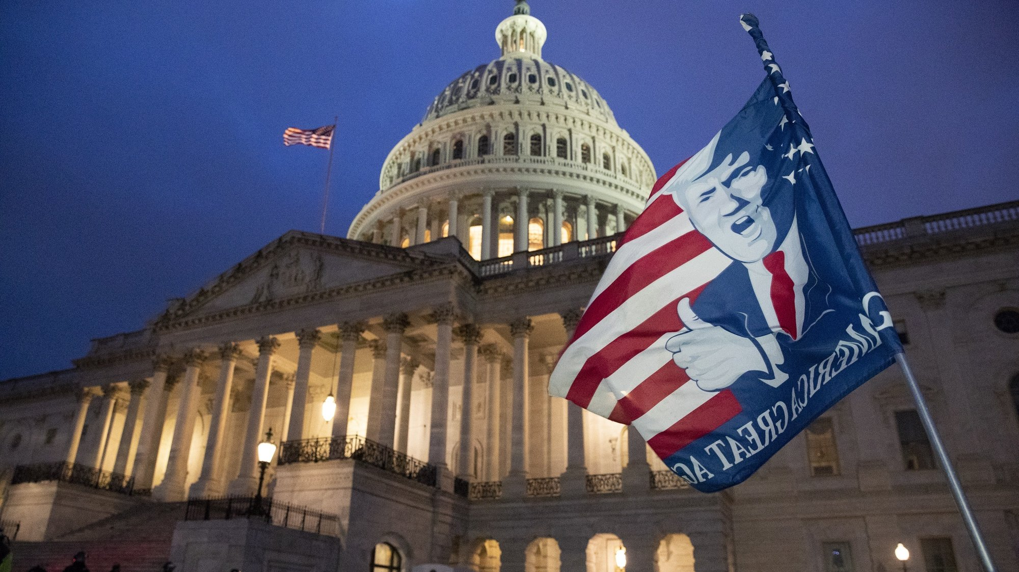 epa08923726 A flag is left by a Trump supporter at the US Capitol at dusk as a curfew begins after pro-Trump protesters stormed the grounds leading to chaos, in Washington, DC, USA, 06 January 2021. Various groups of Trump supporters have broken into the US Capitol and rioted as Congress prepares to meet and certify the results of the 2020 US Presidential election.  EPA/MICHAEL REYNOLDS