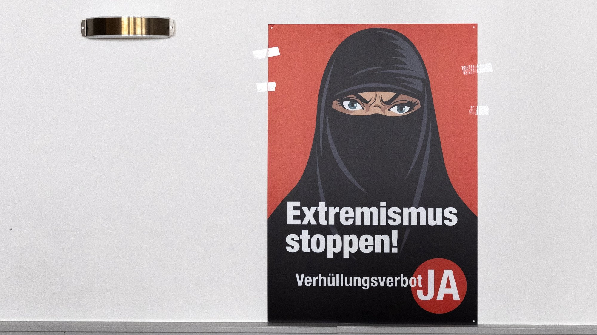 epa09059579 A poster 'Stop Extremism' hangs on a wall at the meeting place of the supporters of the Burqa Ban initiative, in Bern, Switezrland, 07 March 2021. Swiss citizens vote on a proposal to prohibit the concealment of one's face in the public space. Led by right-wing groups, the so-called 'anti-burqa' initiative provides for a ban on the wearing of the niqab, as well as other non-religious forms of face concealment.  EPA/PETER KLAUNZER