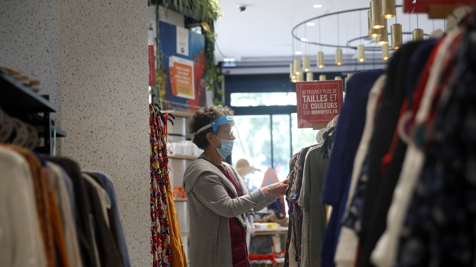 epa08556101 A woman wearing a face mask makes shopping on the Champs Elysee in Paris, France, 20 July 2020. From today, wearing a face mask inside closed public area becomes a duty in an attempt to stop the widespread of the SARS-CoV-2 coronavirus causing the Covid-19 disease.  EPA/YOAN VALAT