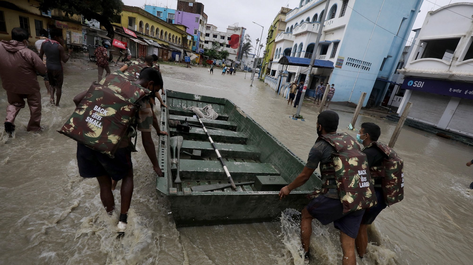epa09228341 Indian Army personel carry a boat to rescue people amid floods as Cyclone Yaas makes landfall in Digha, near the Bay of Bengal, south of Kolkata, India, 26 May 2021. The Odisha and Bengal governments started the evacuation of at-risk areas, as Cyclone Yaas hits the eastern coast of India.  EPA/PIYAL ADHIKARY