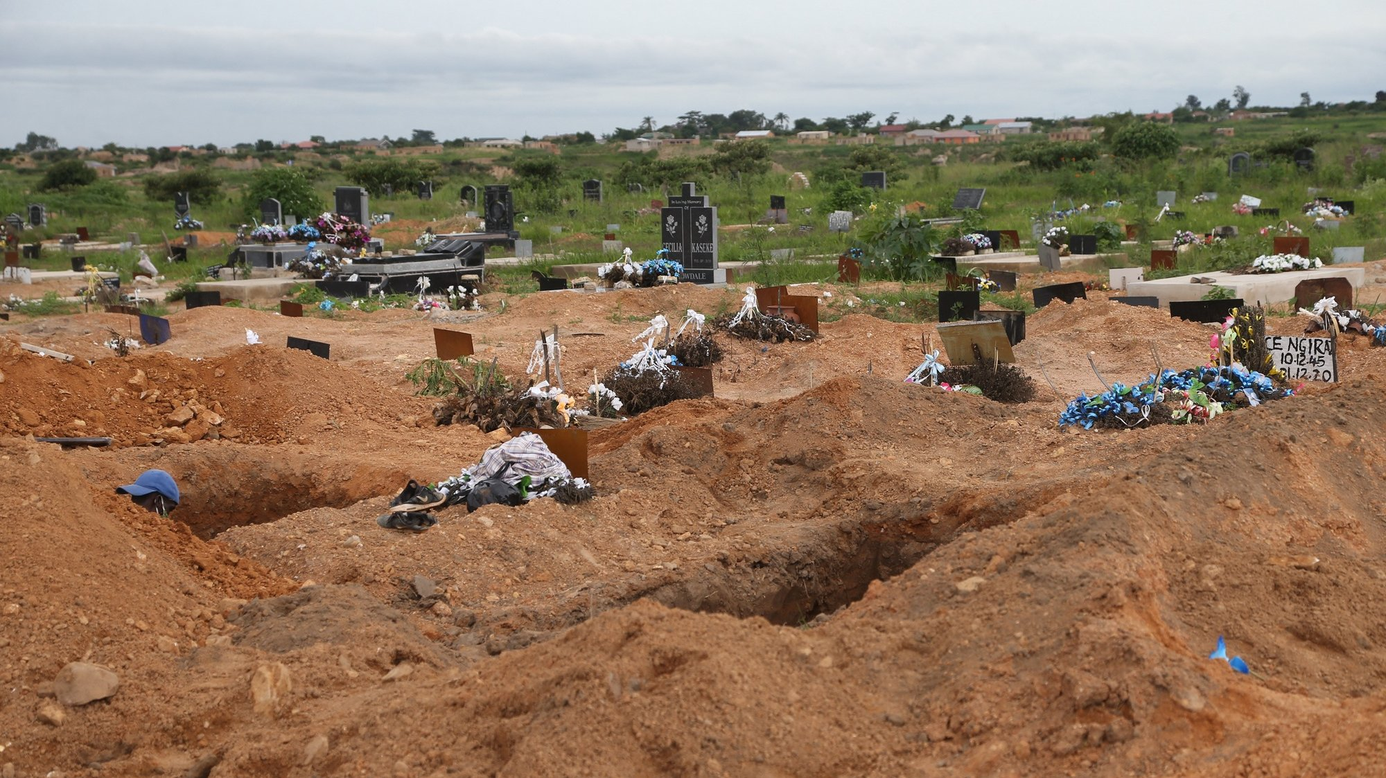 epa08946459 Freshly dug graves waiting for covid -19  victims burial at Zororo Memorial Park, in Chitungwiza, Zimbabwe, 18 January 2021. The country has seen an increase in the number of coronavirus related deaths with an average of 250 fatalities per week since December 2020.            .  EPA/AARON UFUMELI