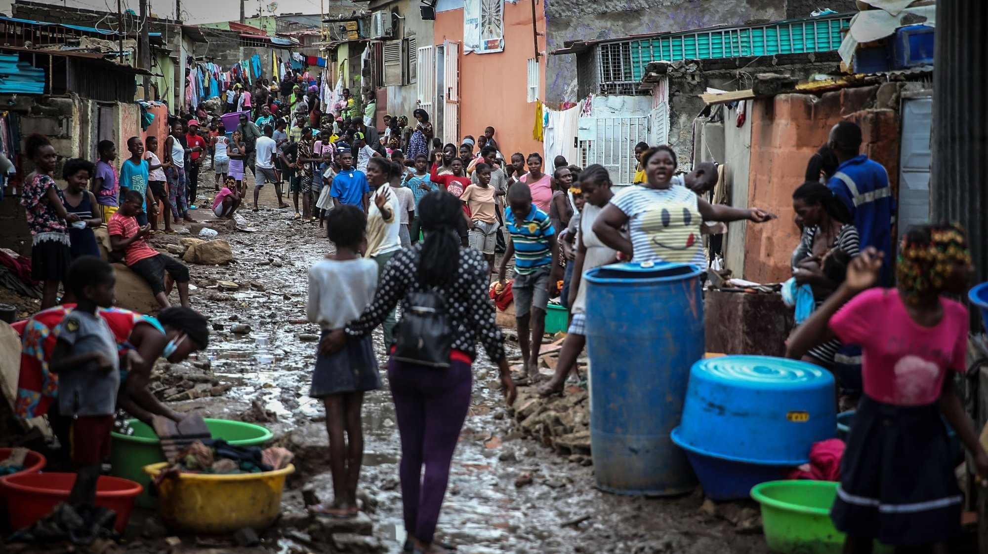 People on a muddy street after heavy rain that fell Monday night in Encide neighborhood, in the Sambizanga district, on the outskirts of Luanda, Angola, 20 April 2021. The torrential rains that hit Luanda on Monday killed 14 people and left 8,000 homeless, with 16 houses collapsed, 15 trees fell, and a bridge was destroyed, among other damages yet to be calculated. AMPE ROGERIO/LUSA