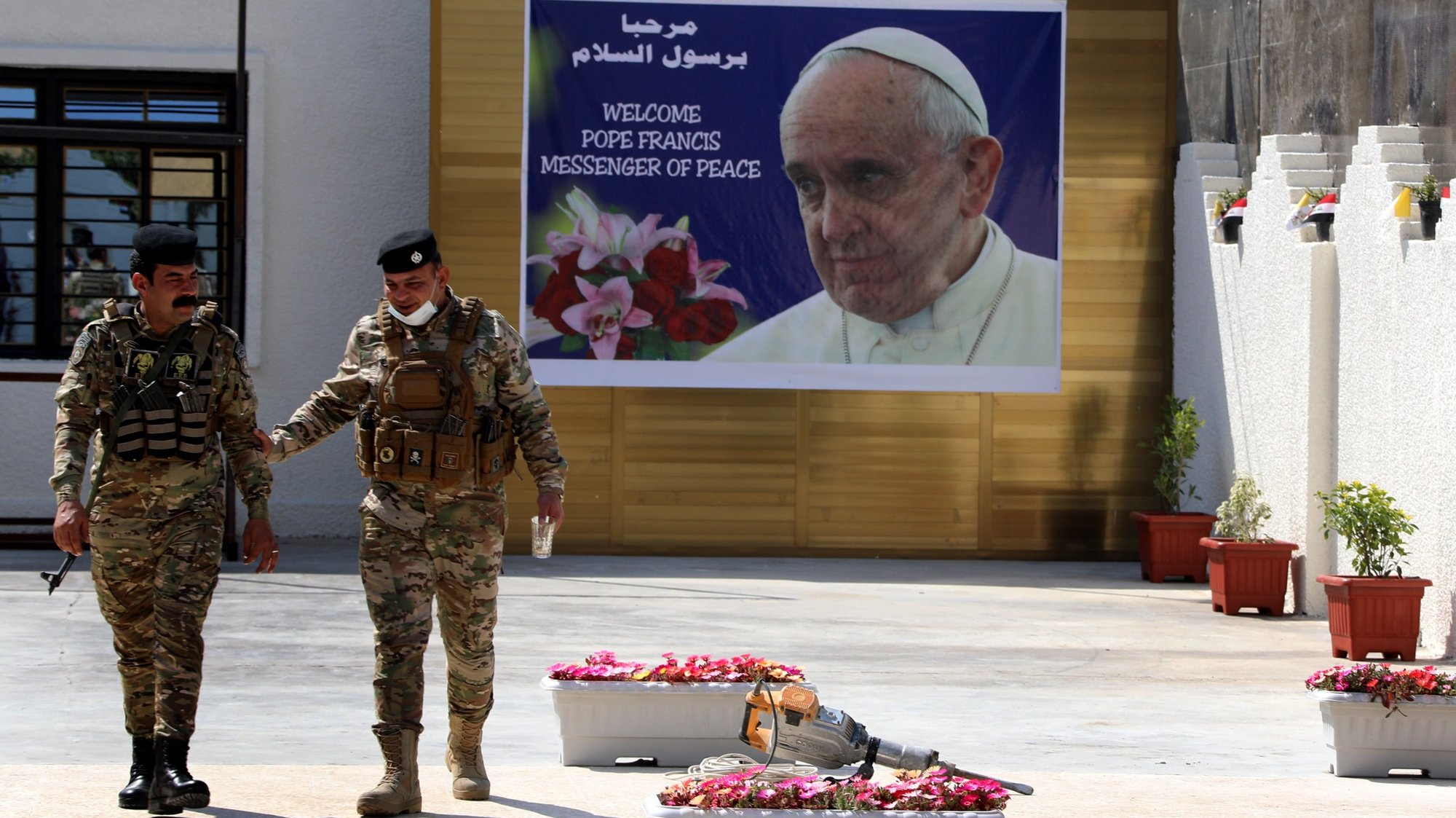 epaselect epa09044899 Iraqi policemen walk next to a posters depicting the picture of Pope Francis at the St. Joseph Chaldean Catholic Church in Baghdad's Karada district, Iraq on 01 March 2021. Pope Francis will visit St. Joseph church in Baghdad, during his trip to Iraq from 05 to 08 March 2021.  EPA/AHMED JALIL