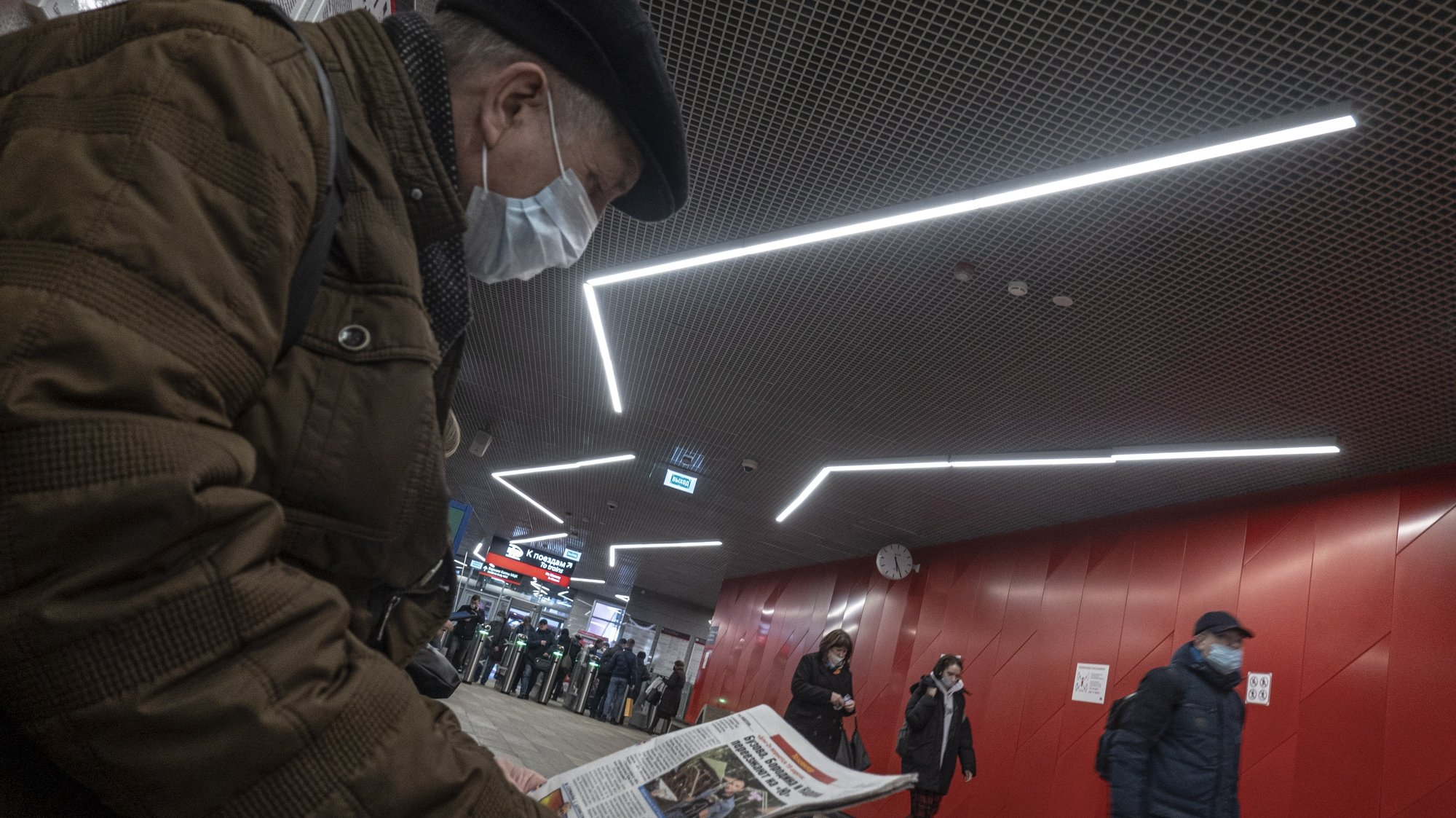 epa09117150 A man wearing a protective face mask reads a newspaper in a station of Moscow metro, Russia, 05 April 2021, amid the COVID-19 coronavirus pandemic.  EPA/SERGEI ILNITSKY
