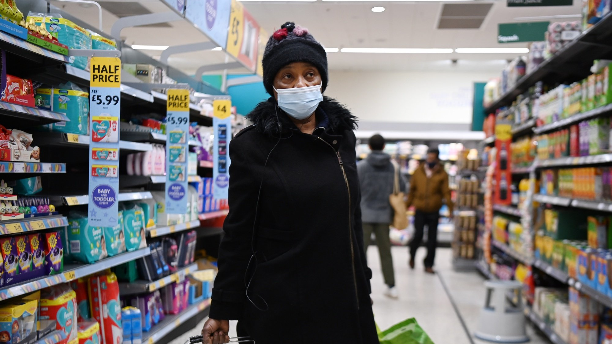 epa08932859 A shopper at a Morrisons supermarket in London, Britain, 12 January 2021. Supermarket chains Morrisons and Sainsbury's have announced that they will enforce stricter shopping measures by insisting on customers wearing face coverings. Britain's national health service (NHS) is coming under severe pressure as Covid-19 hospital admissions continue to rise across the UK.  EPA/ANDY RAIN