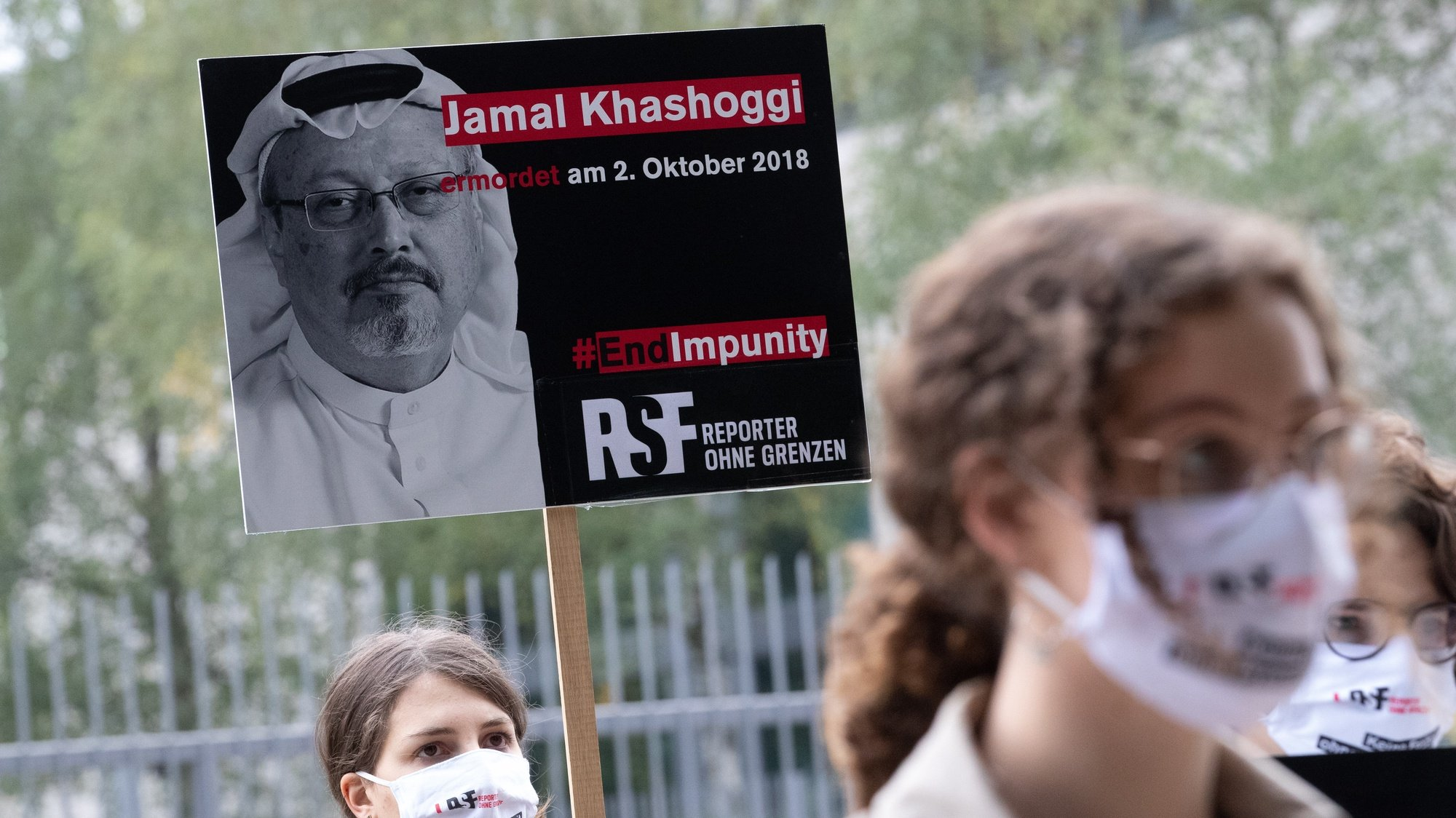 epa08715161 People holding placards reading 'Jamal Khashoggi assasinated 2 October 2018, #EndImpunity' participate in a vigil for the second anniversary of the murdered Saudi journalist Jamal Khashoggi in front of the Saudi-Arabian embassy in Berlin, Germany, 02 October 2020. Washington Post columnist Jamal Khashoggi was killed while visiting the Saudi consulate in Istanbul, Turkey on 02 October 2018 to do a routine paperwork. Three of a total of 11 suspects were given jail sentences of 24 years in total.  EPA/HAYOUNG JEON