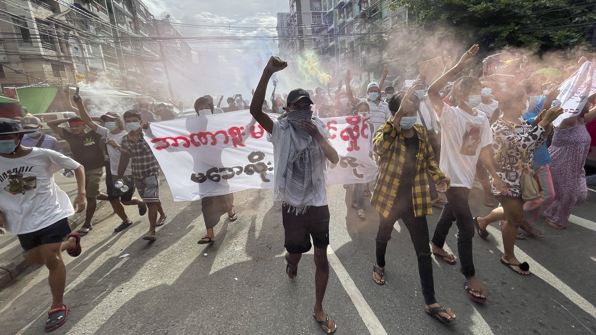 epa09319891 Demonstrators holding posters and flares as they march during an anti-military coup protest at downtown area in Yangon, Myanmar, 03 July 2021. According to the UN Office for the Coordination of Humanitarian Affairs (UN OCHA), at least 230,000 people have been displaced due to violence, armed clashes and insecurity since the military seized power on 01 February 2021.  EPA/STRINGER