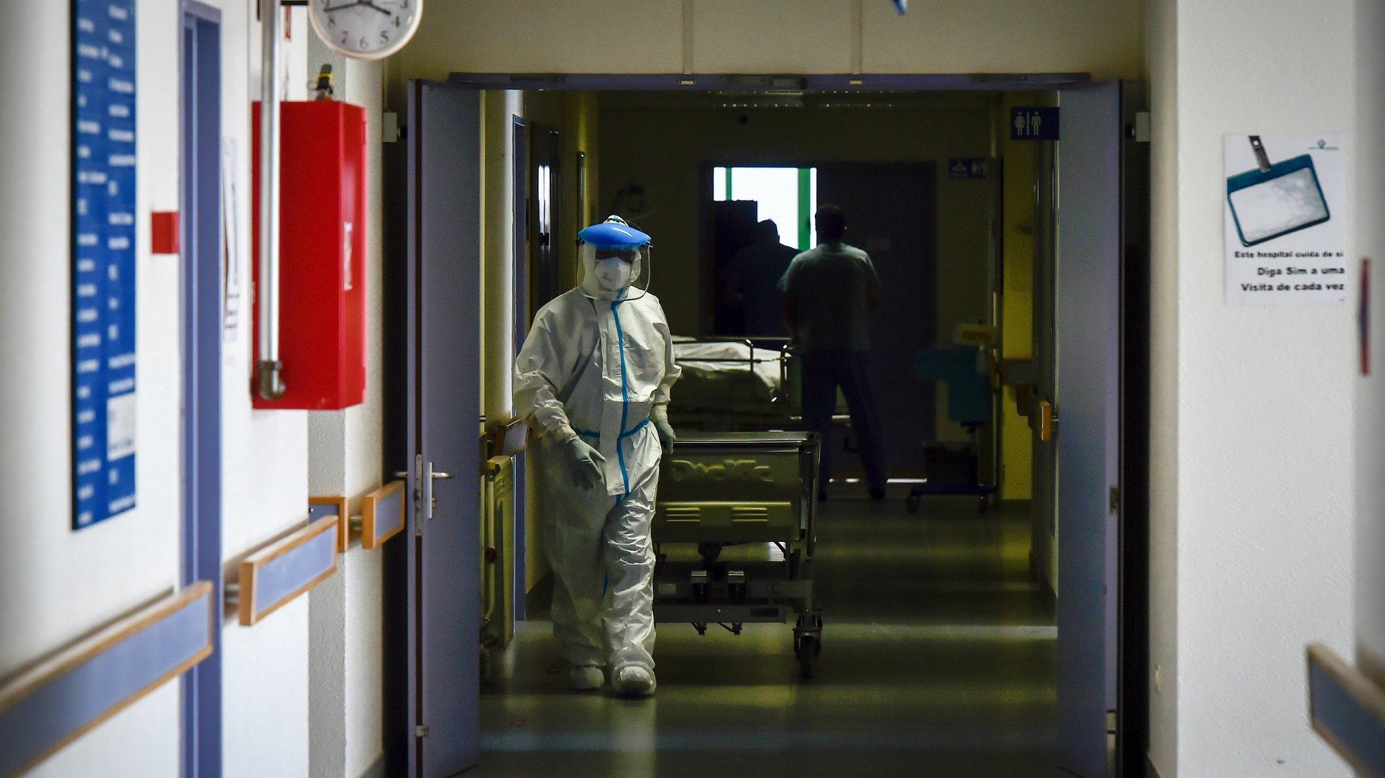 Um assistente operacional da morgue com a maca de transporte de cadáveres, dirige-se para enfermaria do piso 7 do Centro Hospitalar Tondela Viseu (CHTV), dedicado ao tratamento de doentes com covid-19, em Viseu, 09 de março de 2021. (ACOMPANHA TEXTO DA LUSA DO DIA 10 DE MARÇO DE 2021). NUNO ANDRÉ FERREIRA/LUSA