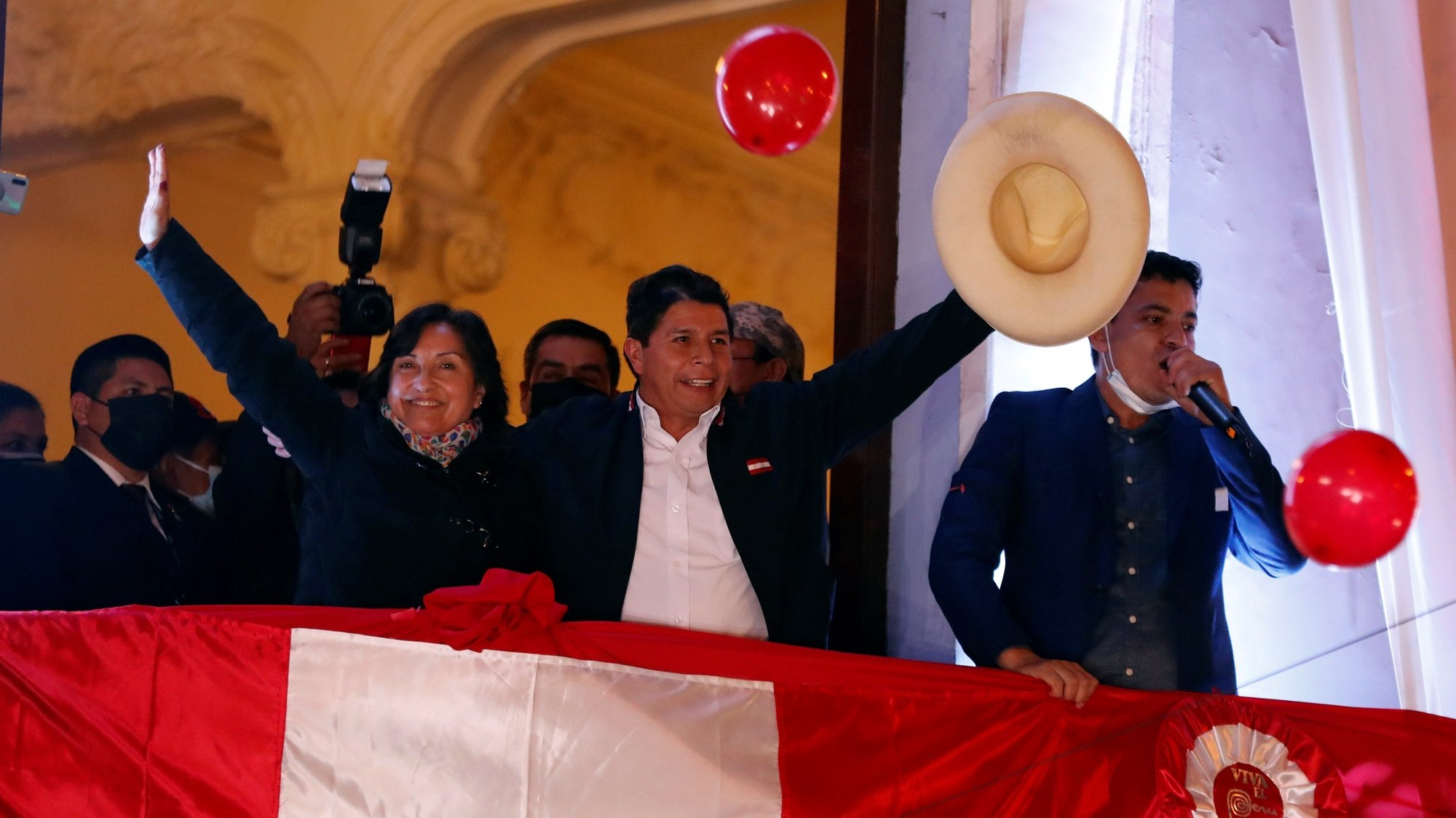 epa09353989 The leftist Pedro Castillo (C), accompanied by his formula to the Vice Presidency Dina Boluarte (L), greets supporters from a balcony after being proclaimed president-elect of the country, in Lima, Peru 19 July 2021. The official proclamation came this Monday, a month and a half after the elections in which he defeated the right-wing Keiko Fujimori, who delayed his appointment with more than a thousand challenges in which she denounced alleged 'fraud' without reliable evidence. After declaring the latest legal appeals presented by Fujimori unfounded, the National Elections Jury (JNE) endorsed the results of the 06 June vote, where Castillo obtained 50.12% of the valid votes, a narrow victory by just 44,263 votes over Fujimori.  EPA/Paolo Aguilar