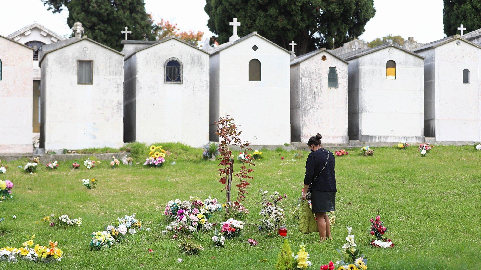 Uma mulher  presta homenagem a um familiar no cemitério de Benfica, no Dia de Todos os Santos, em Lisboa, 01 de novembro de 2020. Este ano, por causa da covid-19, o Governo decretou a proibição de circulação entre concelhos de 30 de outubro até dia 3 de Novembro, mas os cemitérios de Lisboa mantêm-se abertos, com algumas restrições, como o uso de máscara e o controlo de entradas. ANTÓNIO PEDRO SANTOS/LUSA