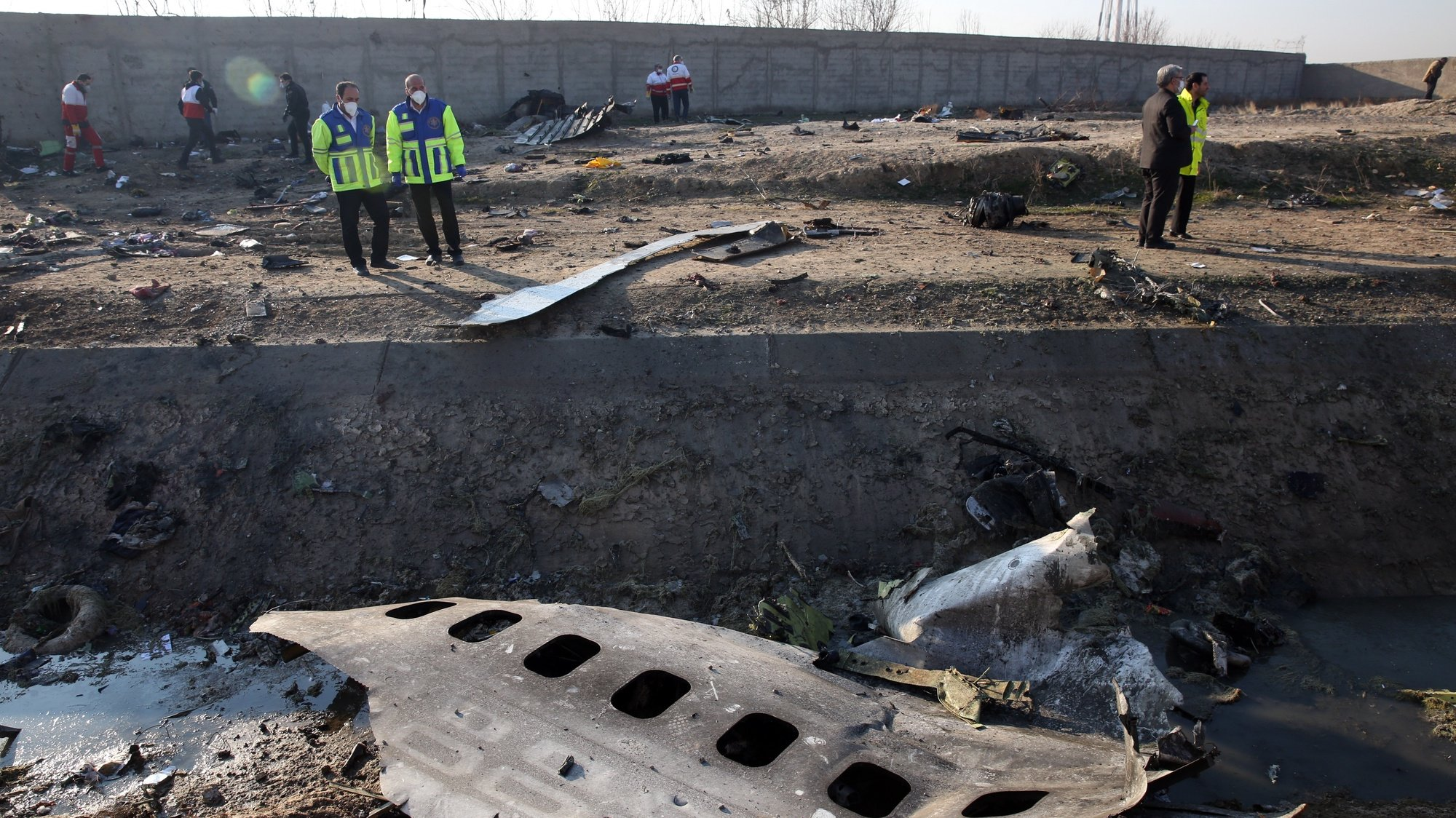 epa08553428 (FILE) - Officials stand near the wreckage after an Ukraine International Airlines Boeing 737-800 carrying 176 people crashed near Imam Khomeini Airport in Tehran, killing everyone on board; in Shahriar, Iran, 08 January 2020 (reissued 18 July 2020). Media reports state on 18 July 2020 that Iran has sent to France the black box of the Ukrainian passenger plane, which was accidentally downed by Iranian armed forces on 08 January 2020 near Tehran, killing all 176 people aboard, after mistaking it for an incoming missile. The black box will be read in Paris on 20 July 2020, media added. *** Local Caption *** 55750844