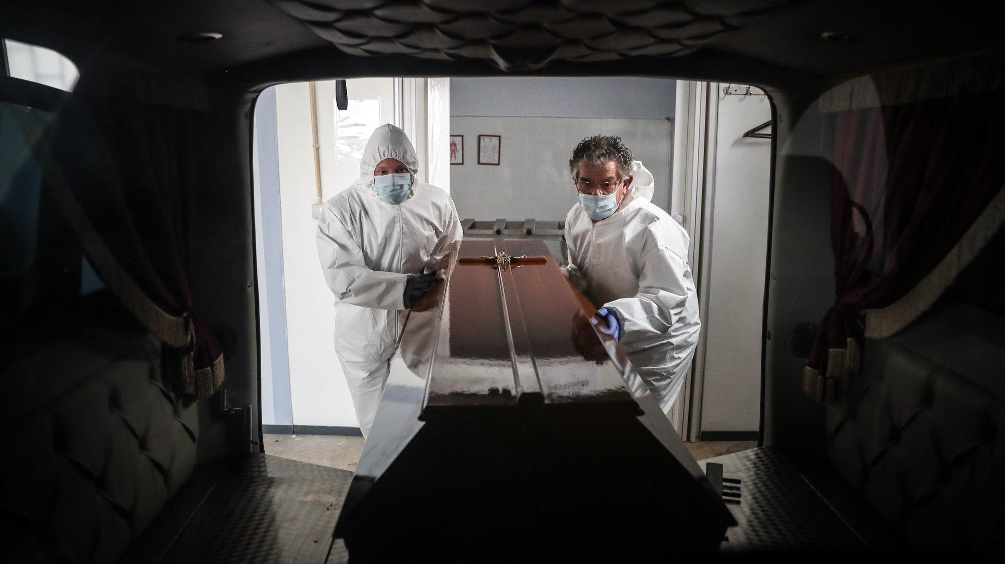 (11/23) Funcionários de uma agência funerária colocam um caixão de uma mulher que morreu vítima de covid-19 no interior de uma carrinha funerária, na Amadora, 30 de janeiro de 2021. Esta semana Portugal ultrapassou as 300 mortes diárias por covid-19, um novo máximo desde o início da pandemia. (ACOMPANHA TEXTO DA LUSA DO DIA 30 DE JANEIRO DE 2021). MÁRIO CRUZ/LUSA