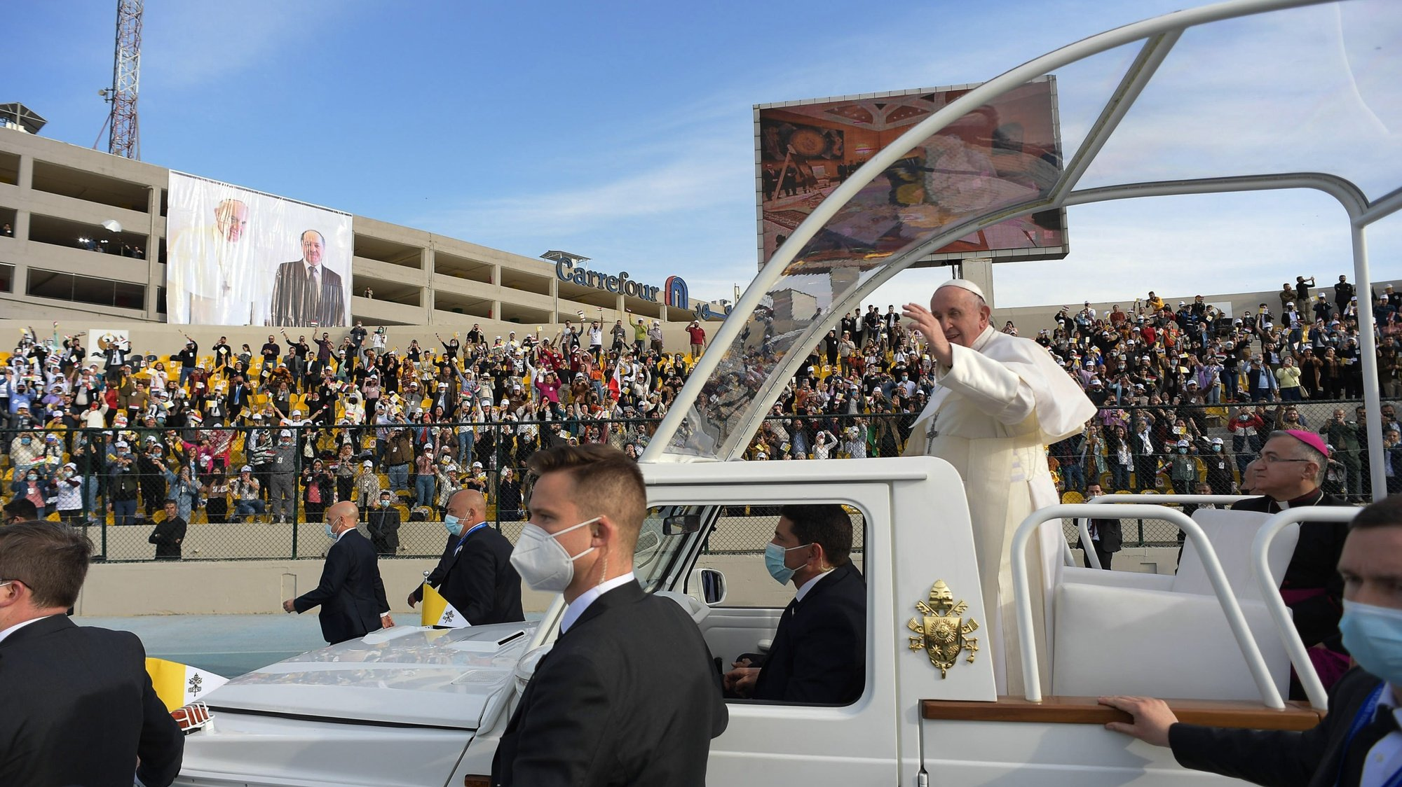 epa09059524 Pope Francis (C) waves to faithful from the Papal Mobil as he arrives to celebrate the Holy Mass at the 'Franso Hariri' Stadium in Erbil, Iraq, 07 March 2021. Pope Francis began on 05 March a three-day official visit in Iraq, the first papal visit to this country affected throughout the years by war, insecurity and lately COVID-19 Coronavirus pandemic.  EPA/VATICAN MEDIA HANDOUT  HANDOUT EDITORIAL USE ONLY/NO SALES