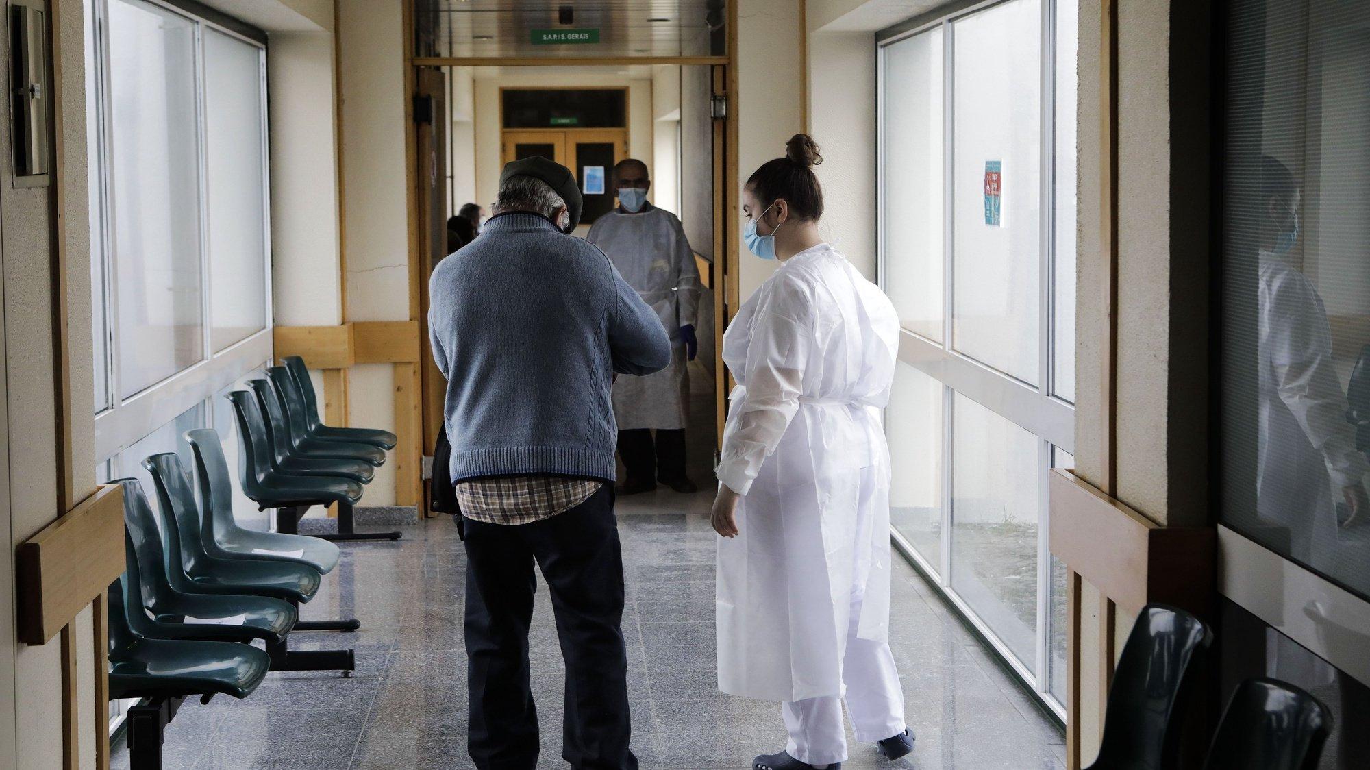 """Um idoso é vacinado contra a covid-19 por um profissional de saúde no Centro de Saúde de Fornos de Algodres, 12 de março de 2021. Idosos residentes em Penalva do Castelo, distrito de Viseu, e Fornos de Algodres, distrito da Guarda, encaram a vacinação como forma de combater a """"guerra"""" que o mundo trava contra a covid-19. (ACOMPANHA TEXTO DA LUSA DO DIA 27 DE MARÇO DE 2021). MIGUEL PEREIRA DA SILVA/LUSA"""