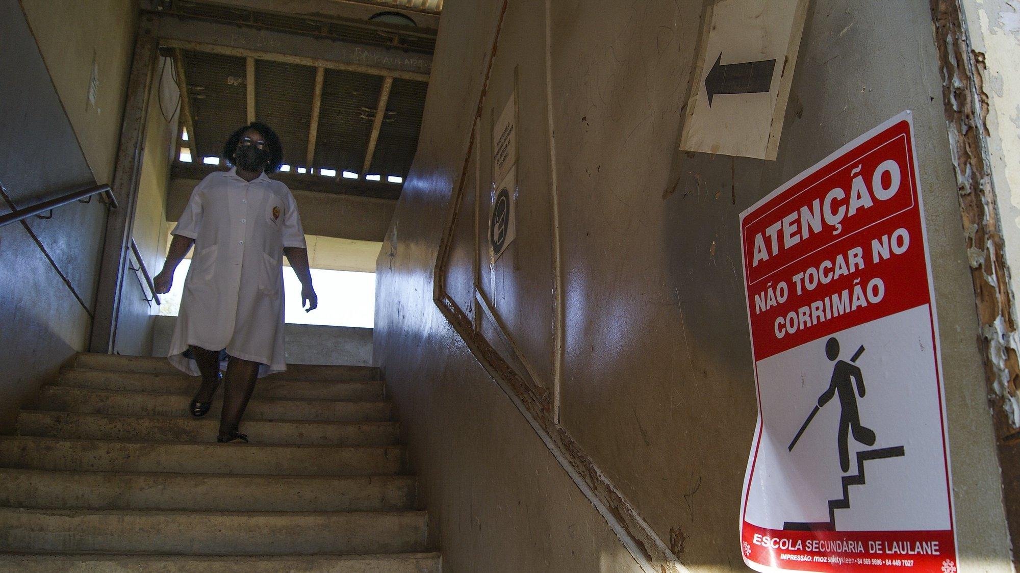 """Um cartaz de informação no acesso às escadas de uma escola onde se lê """"Atenção, Não Tocar no Corrimão"""", no primeiro dia do regresso às aulas devido à covid-19, em Maputo, Moçambique, 22 de março de 2021. Moçambique viveu em estado de emergência entre abril e setembro de 2020, vigorando desde então o estado de calamidade, designações legais para enquadrar diversas restrições com vista à prevenção da covid-19, que incluíram a suspensão das aulas. LUÍSA NHANTUMBO/LUSA"""
