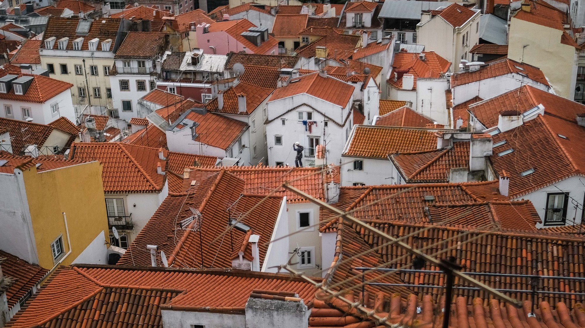 Um trabalhador nos telhados de Alfama, em Lisboa, 18 de junho de 2021. O Governo decidiu proibir as deslocações de e para a Área Metropolitana de Lisboa (AML) no fim de semana devido à subida dos casos de covid-19 neste território. MÁRIO CRUZ/LUSA
