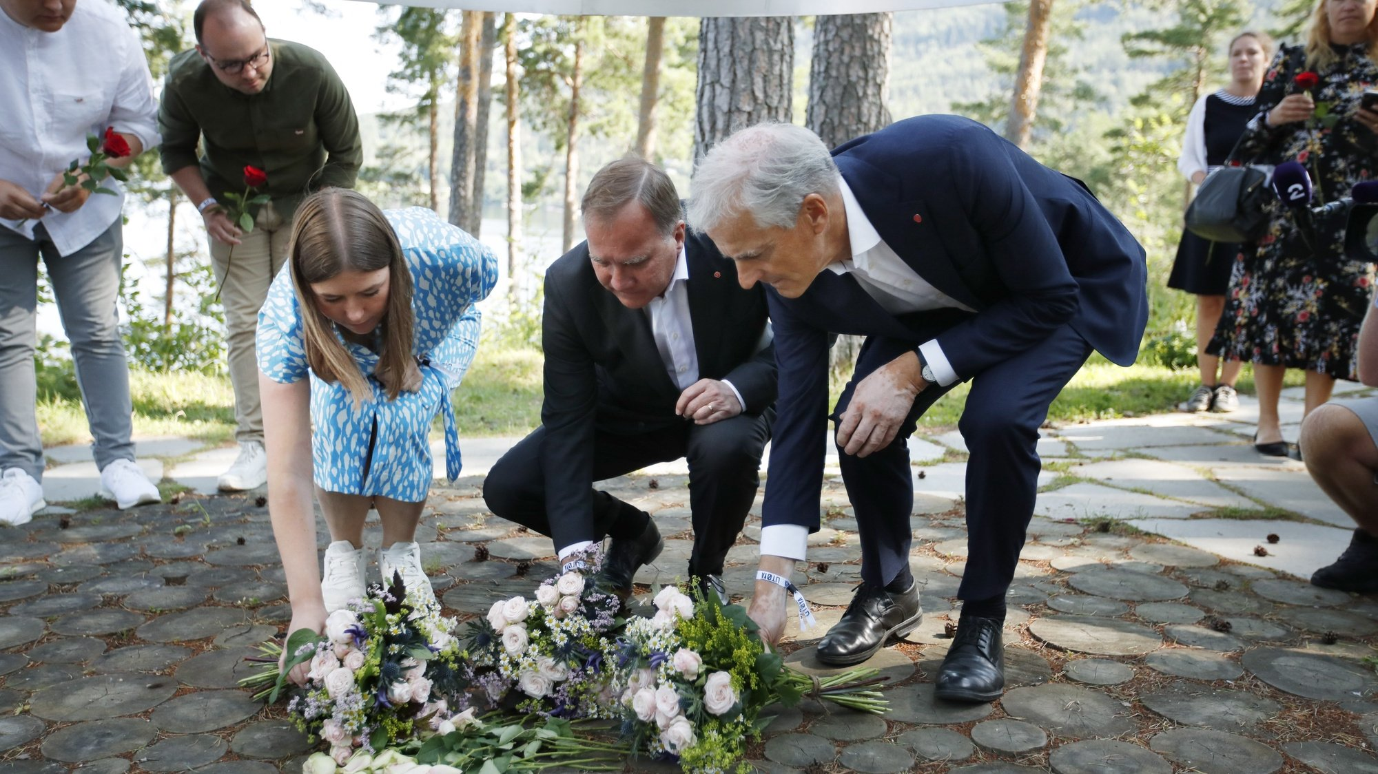 epa09356447 Leader of AUF in Norway, Astrid Hoem, Prime Minister of Sweden Stefan Loefven and leader of the Norwegian Labor Party Jonas Gahr Store lay flowers at the memorial on Utoya the day before the 10th anniversary of the terrorist attack on 22 July 2011. Norway marks 10 years since 22 July 2011, when 77 people were killed by an act of terrorism, eight in the governmental quarters in Oslo, and 69 at the Social Democratic Youth party's summer camp on the island of Utoya.  EPA/BEATE OMA DAHLE  NORWAY OUT