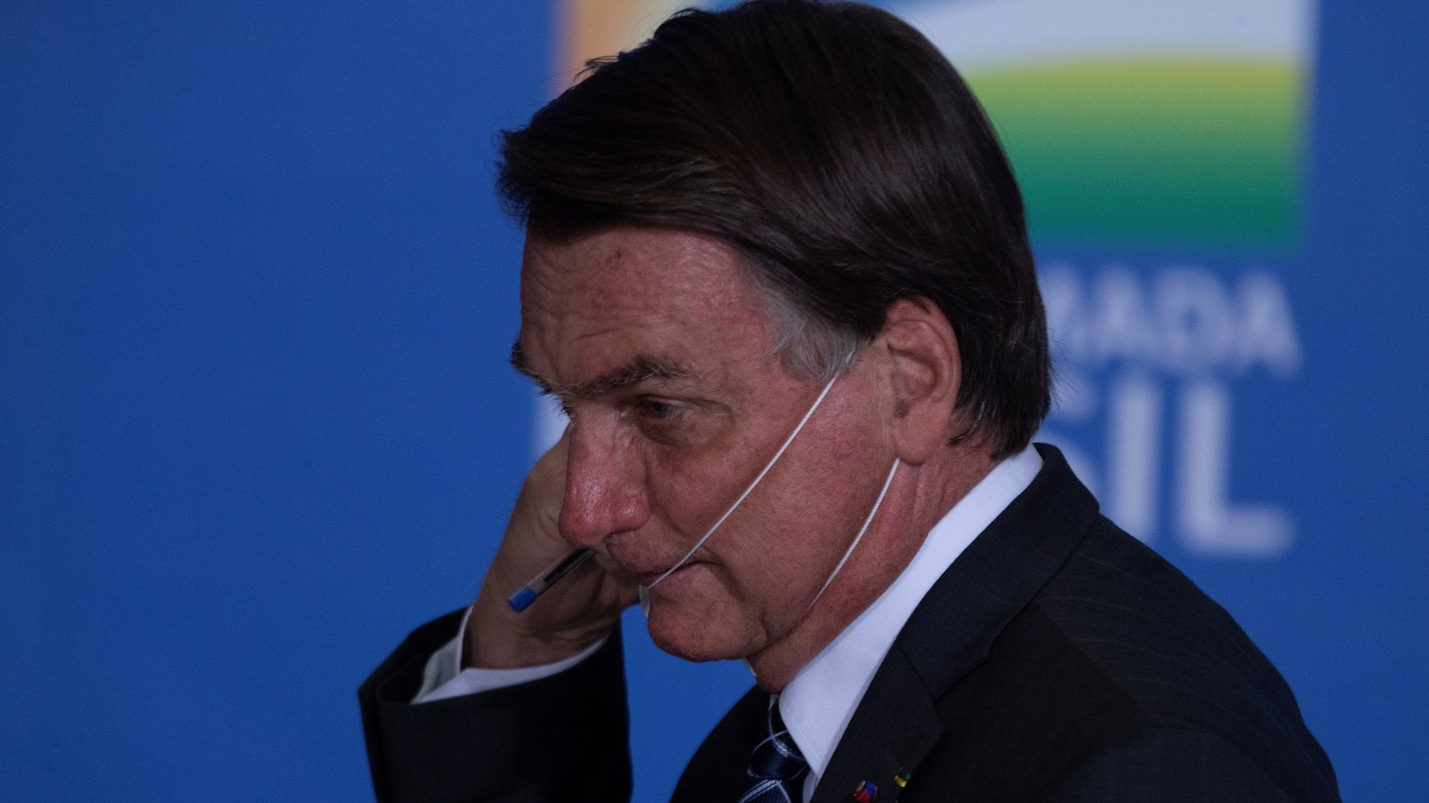 epa09294580 Brazilian President Jair Bolsonaro removes his face mask during the launching of an agriculture program at Planalto Presidential Palace in Brasilia, Brazil, 22 June 2021. Brazil's Goverment announced some US $50 billion for investments in agriculture during 2021-2022.  EPA/Joédson Alves