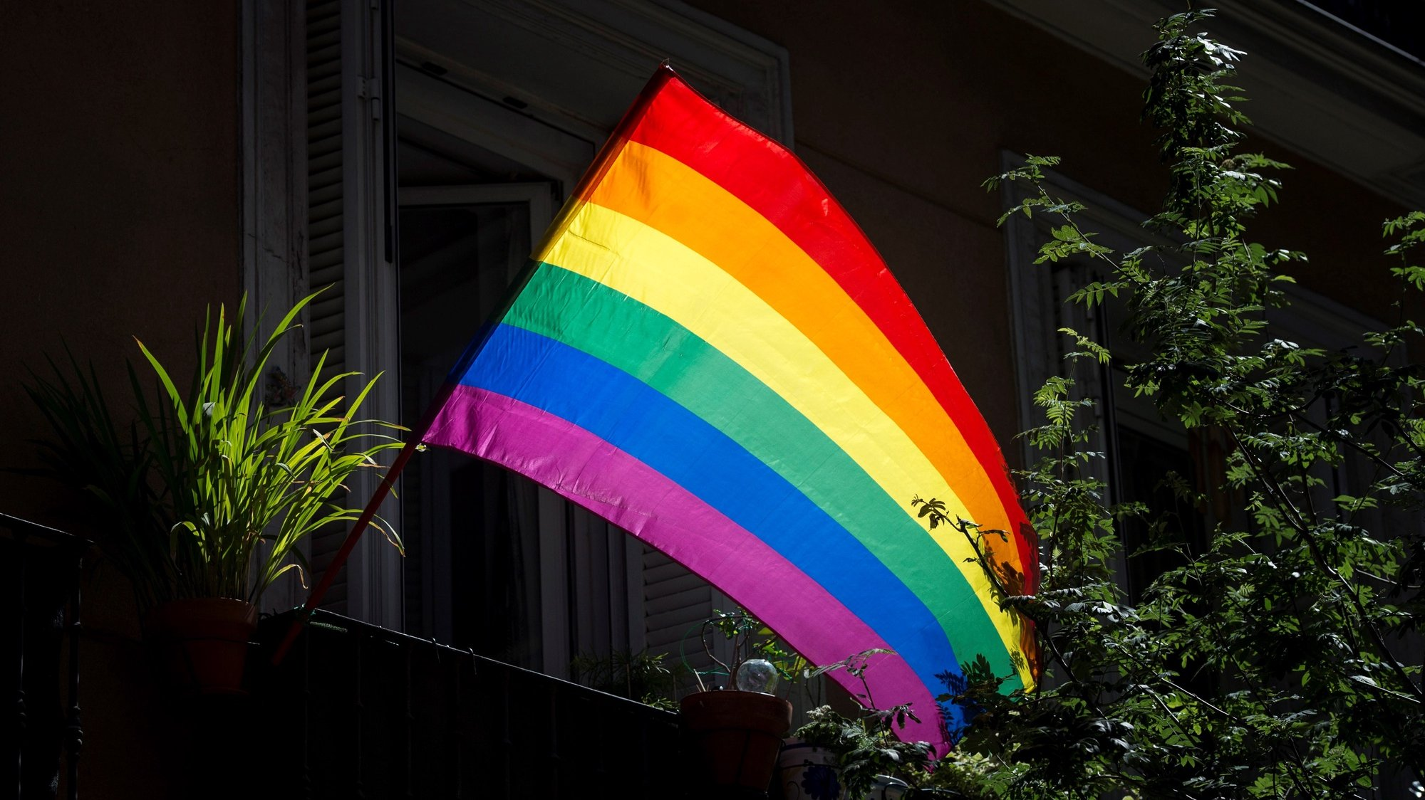epa08511670 A rainbow flag is seen at the window of a flat in Chueca, known as the 'gay neighborhood', in Madrid, Spain, 27 June 2020.  EPA/Luca Piergiovanni
