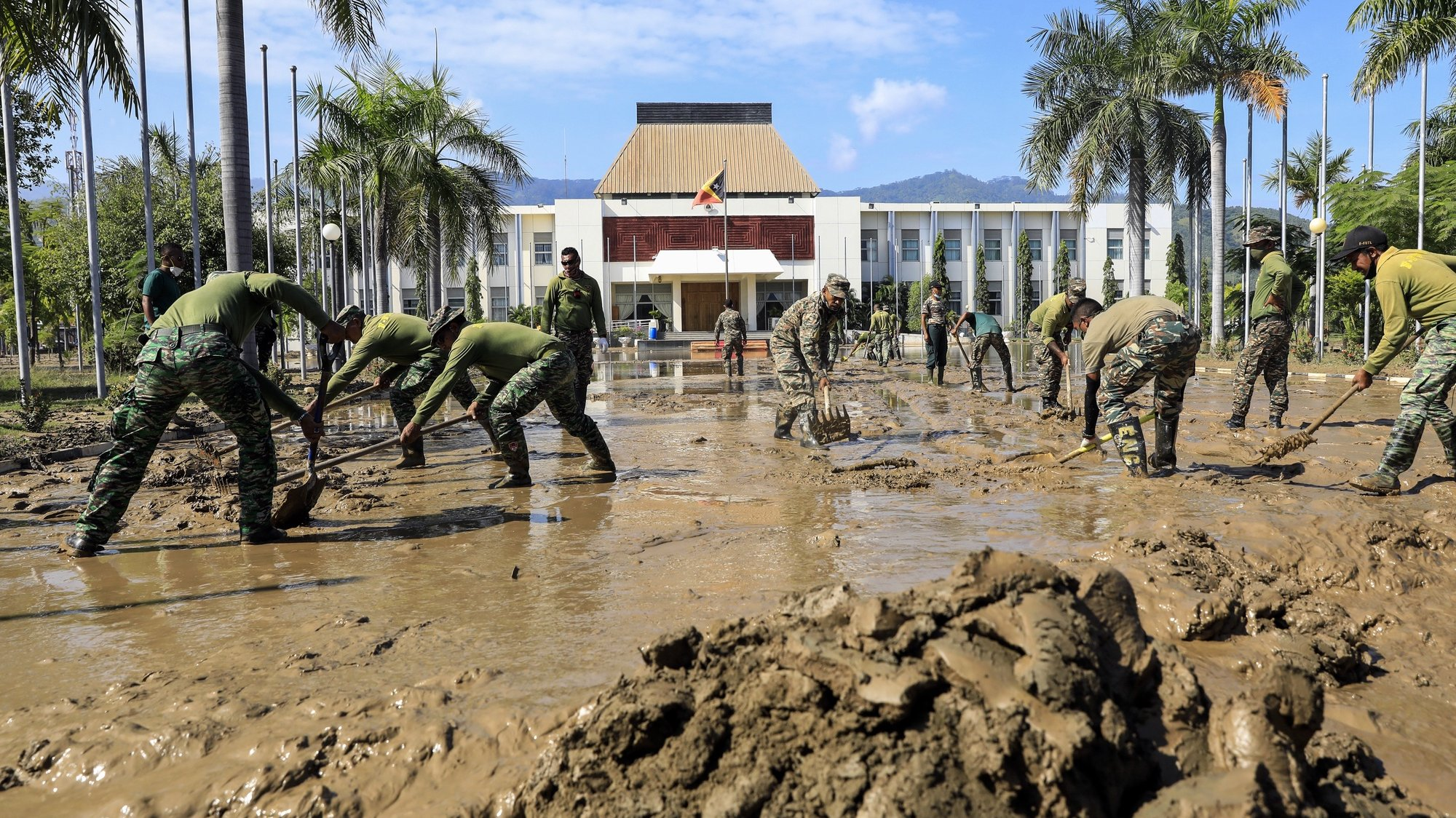 epa09121775 East Timorese military personnel clean up the mud outside the presidential office in the aftermath of floods in Dili, East Timor, also known as Timor Leste, 08 April 2021. More than 100 people were killed and dozens went missing in Indonesia and East Timor as floods and landslides caused by torrential rains hit over the weekend.  EPA/ANTONIO DASIPARU