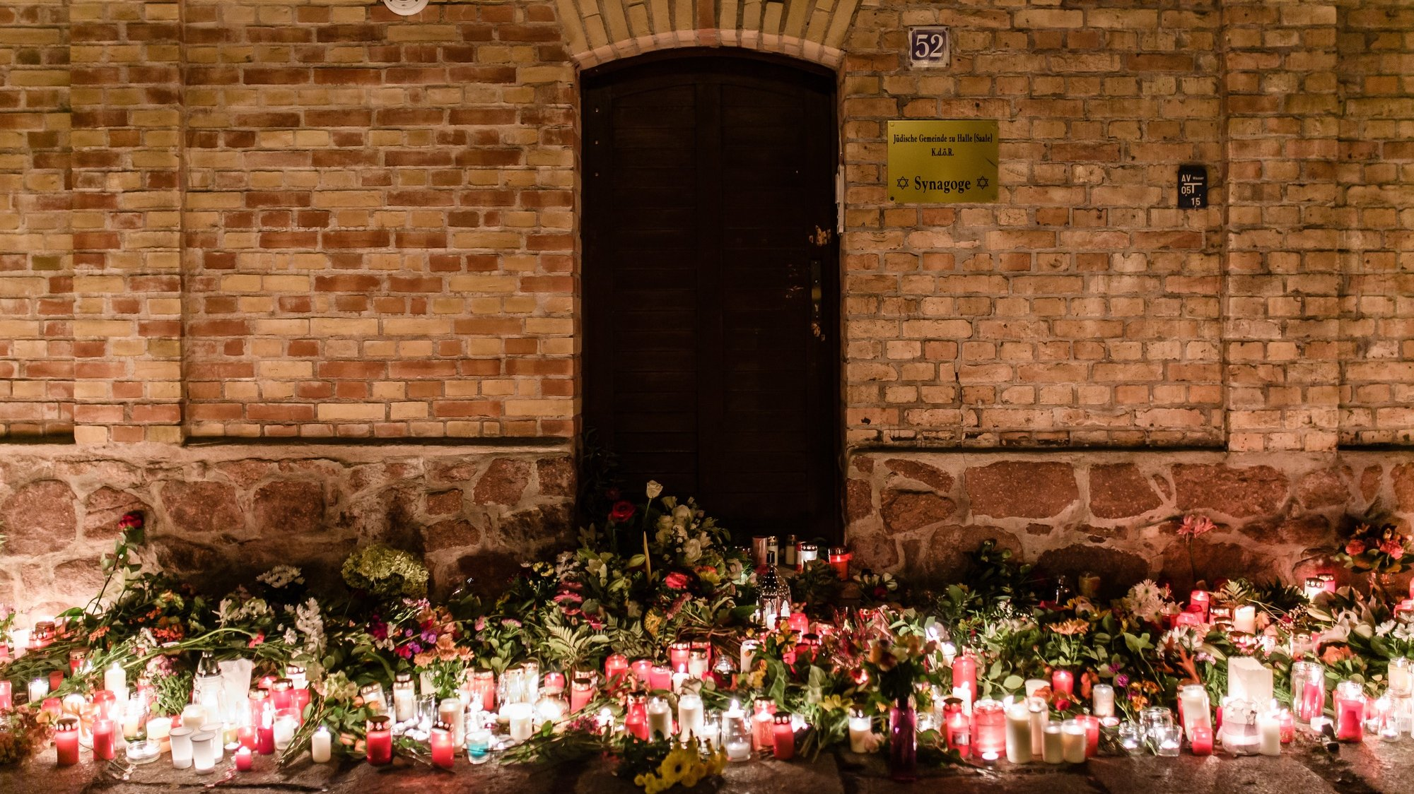 epa08891360 (FILE) - Candles and flowers are laid in front of the synagogue after an attack in which a man went on rampage shooting and tried to enter the Halle synagogue during celebrations of Yom Kippur, in Halle Saale, Germany, 10 October 2019 (reissued 18 December 2020). The trial of the Halle syangogue shooting is expected to end on 21 December.  EPA/CLEMENS BILAN *** Local Caption *** 55538431