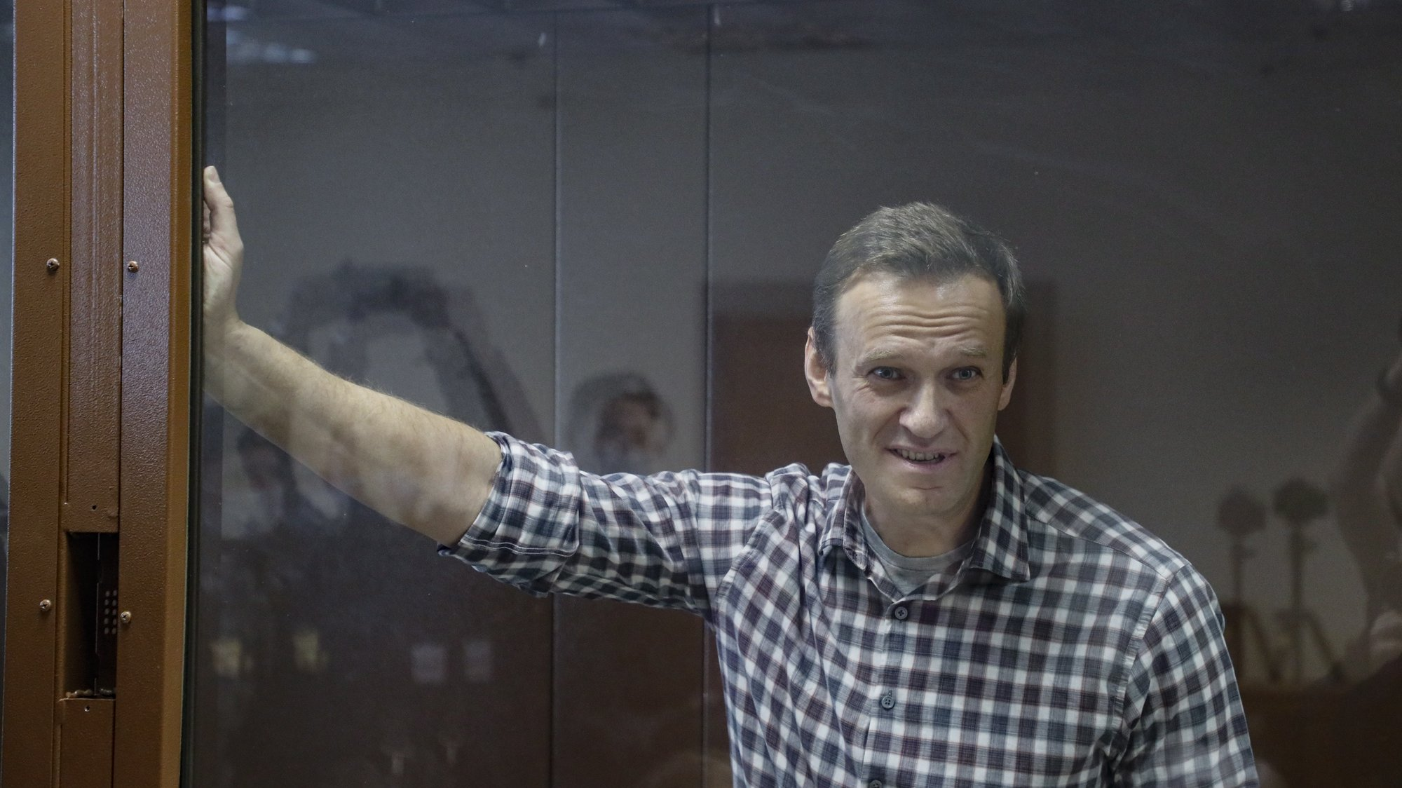 epa09025238 Russian opposition leader Alexei Navalny stands inside a glass cage prior to a hearing at the Babushkinsky District Court in Moscow, Russia, 20 February 2021. The Moscow City court will hold a visiting session at the Babushkinsky District Court Building to consider Navalny's lawyers appeal against a court verdict issued on 02 February 2021, to replace the suspended sentence issued to Navalny in the Yves Rocher embezzlement case with an actual term in a penal colony.  EPA/YURI KOCHETKOV MANDATORY CREDIT