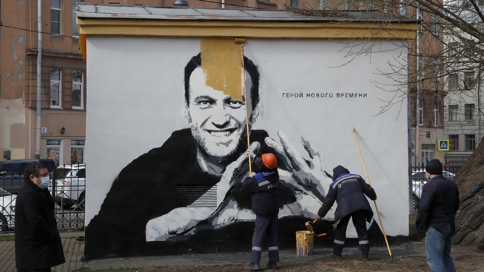 epaselect epa09164791 Municipal workers paint over a graffiti depicting jailed Russian opposition politician Alexei Navalny with wordings reading, 'The hero of the new age', in St. Petersburg, Russia, 28 April 2021. Navalny is currently being held at a prison camp northeast of Moscow, sentenced to imprisonment at the penal camp in early February 2021 for violating parole requirements related to an earlier suspended sentence over 2014 embezzlement charges.  EPA/ANATOLY MALTSEV