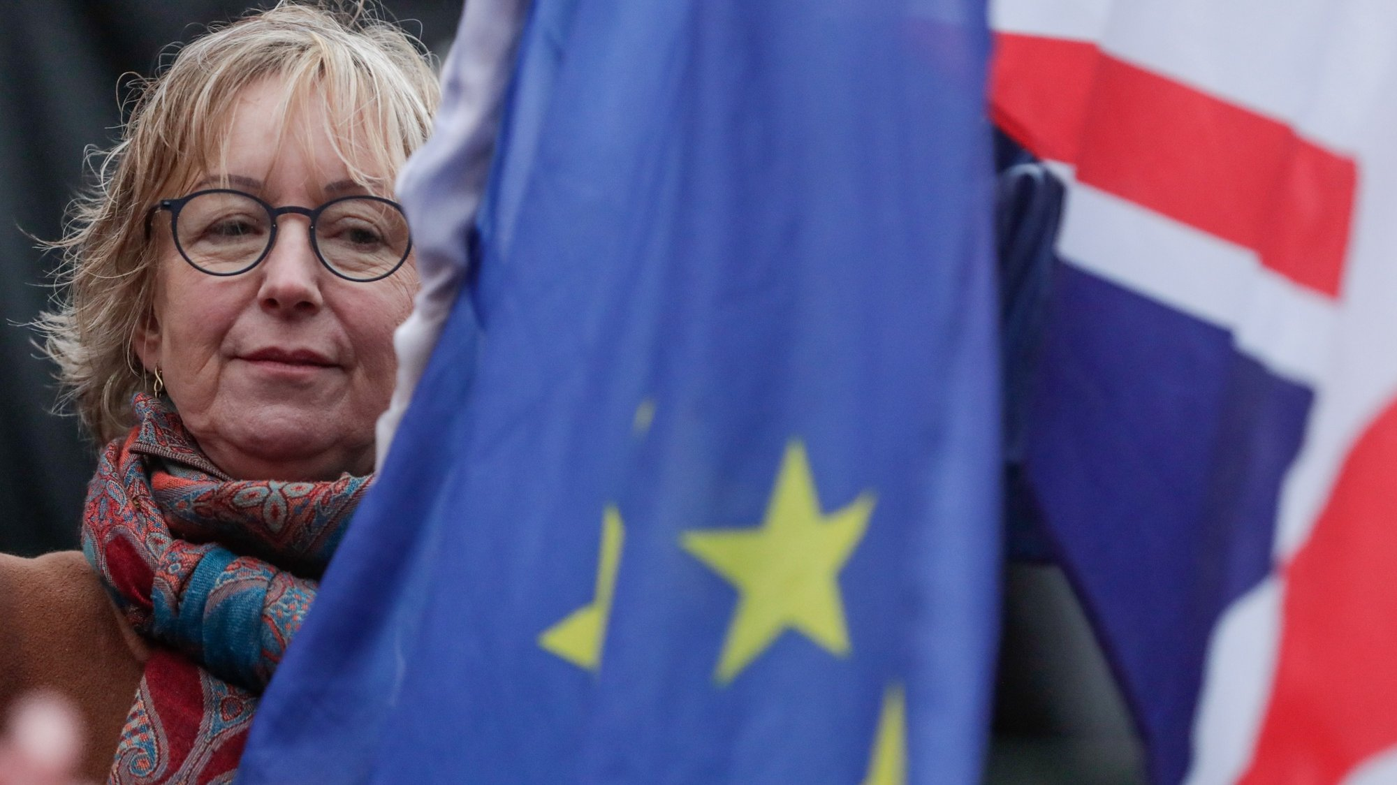 epa08179430 A woman holds a European flag and a Union Jack flag on the Grand Place in Brussels, Belgium, 30 January 2020. The city of Brussels is organizing the 'Brussels Calling' event to underline its long friendship with the British. The UK will leave the EU on 31 January 2020.  EPA/STEPHANIE LECOCQ