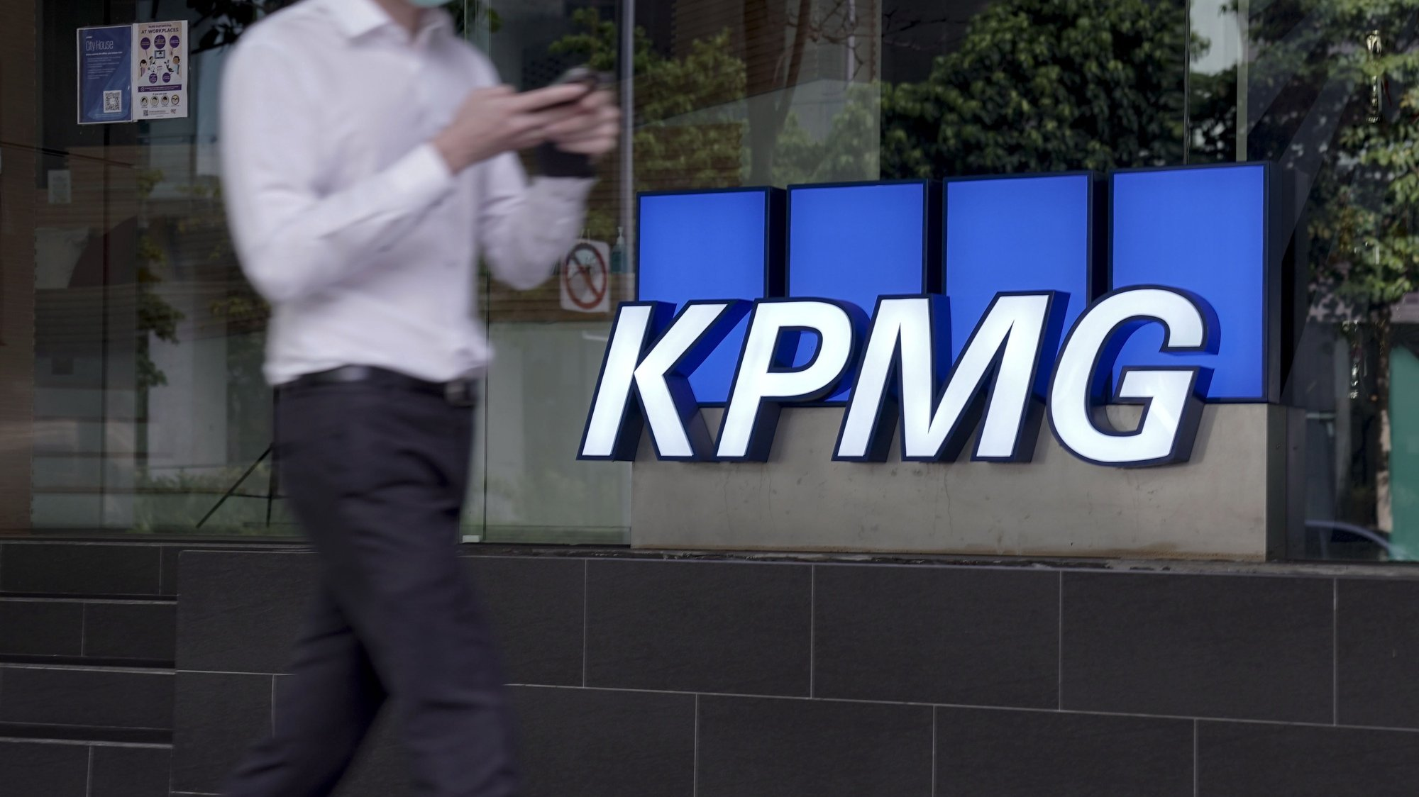 epa08777182 A man walks past the logo of auditing firm KPMG in the financial district in Singapore, 27 October 2020. The fallout of the global Covid-19 coronavirus pandemic has had a range of effects across workers from different sectors of the economy. As businesses gradually open up, economists are describing a 'K-shaped' recovery caused by lower wage workers affected by health and safety regulations, while white collar workers remain largely unaffected due to the advent of telecommuting and work from home arrangements.  EPA/WALLACE WOON