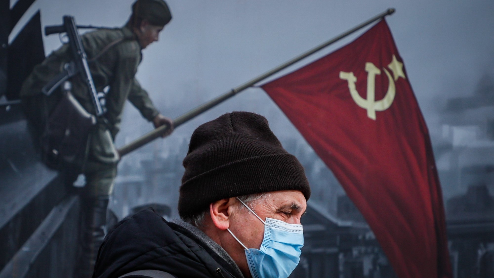 epaselect epa09046553 Russian man wearing a protective face mask walks on the street in front of a painting depicting the defeat of the Nazis in World War II in Moscow, Russia, 02 March 2021.  EPA/YURI KOCHETKOV