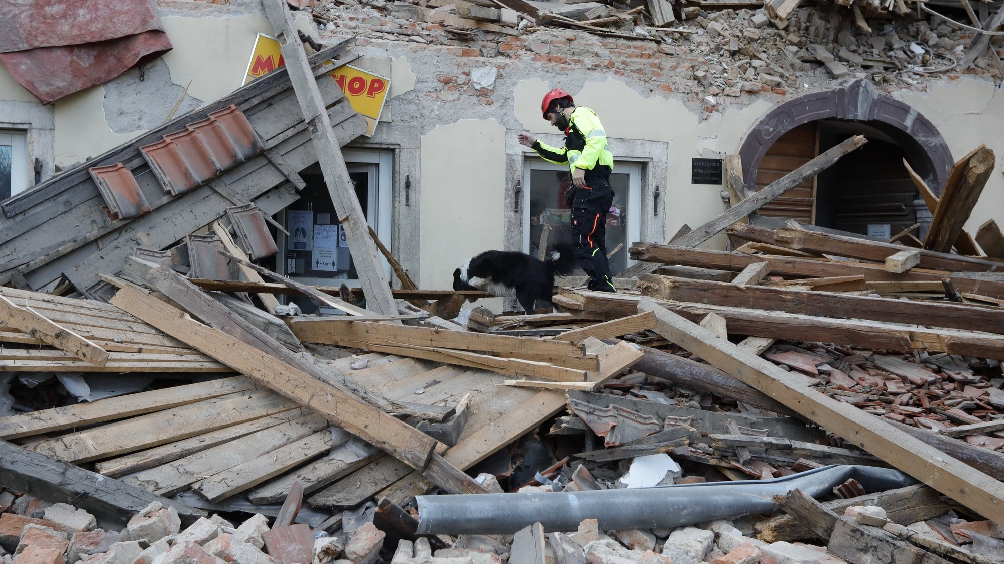 epa08909778 A rescue worker and his dog inspect buildings damaged in an earthquake in Petrinja, Croatia, 29 December 2020. A 6.4 magnitude earthquake struck around 3km west south west of the town with reports of many injuries and at least one death.  EPA/ANTONIO BAT