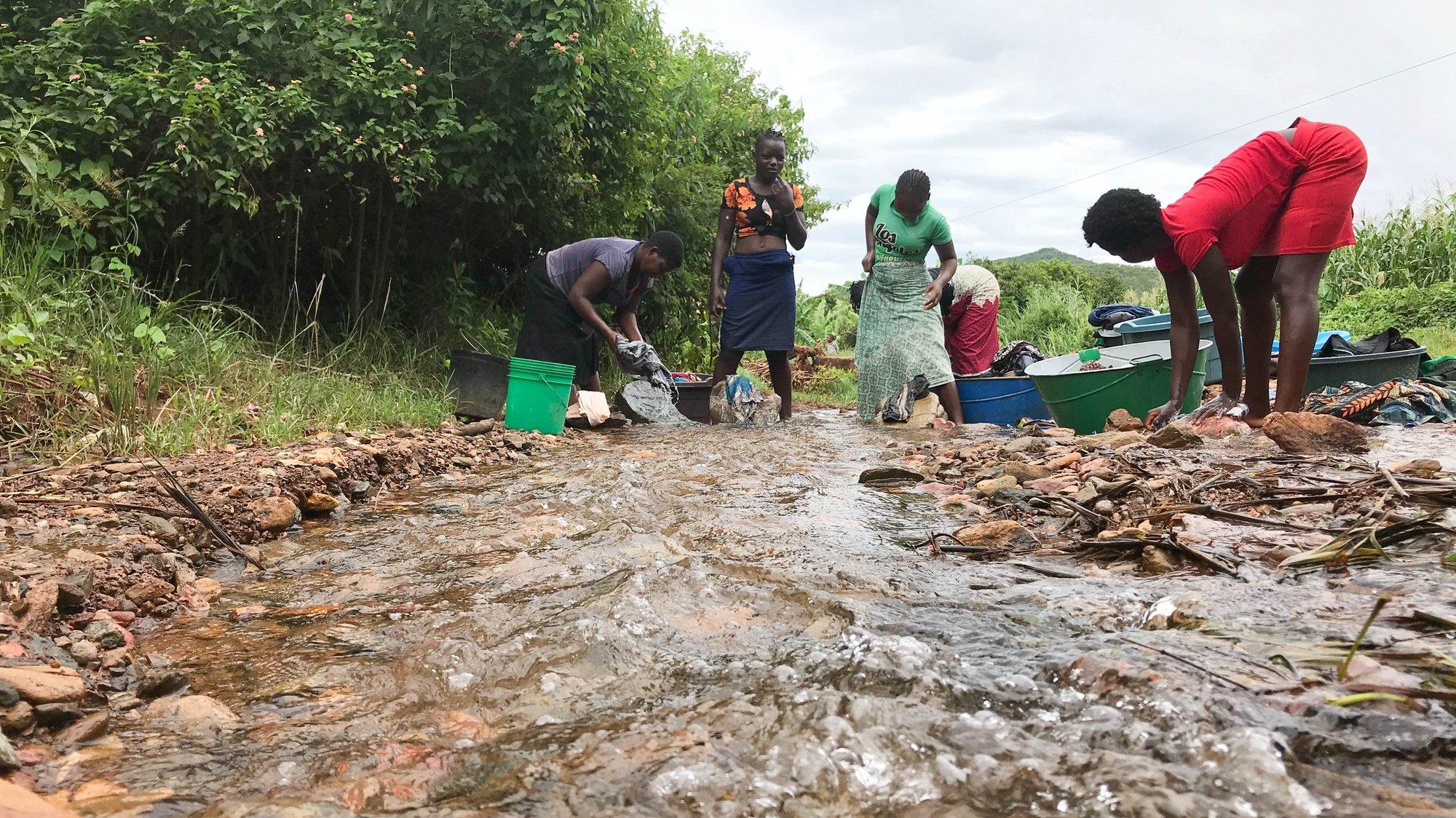 Mulheres lavam a roupa num ribeiro no distrito de Manica, Moçambique, 26 de fevereiro de 2021. Um total de 92 crianças foram identificadas pelos 114 Comités Comunitários de Proteção a Criança, criados pela Save The Children, como estando em situação de risco de uniões prematuras em 2020 nos distritos de Manica, Machaze, Macossa e Tambara, tendo 47 sido resgatadas. (ACOMPANHA TEXTO DA LUSA DO DIA 02 DE MARÇO DE 2021). ANDRÉ CATUEIRA/LUSA