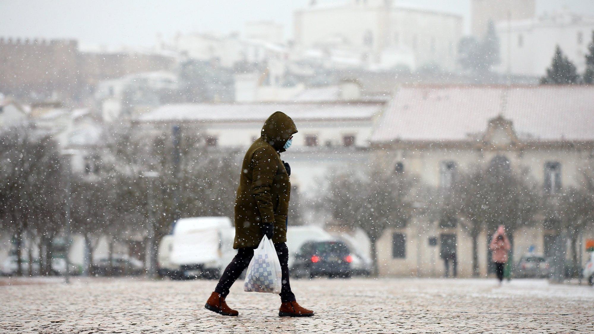 Uma popular circula no Rossio de Estremoz momentos após um forte nevão nesta cidade, fenómeno meteorológico raro no alentejo. Não nevava no distrito de Évora há 12 anos. Estremoz, 09 de janeiro de 2021. O Instituto Português do Mar e da Atmosfera (IPMA) mantêm o continente e a Madeira em alerta amarelo devido ao frio previsto para o fim-de-semana, e prevê que a temperatura média da próxima semana esteja abaixo dos valores normais para a época.  NUNO VEIGA/LUSA