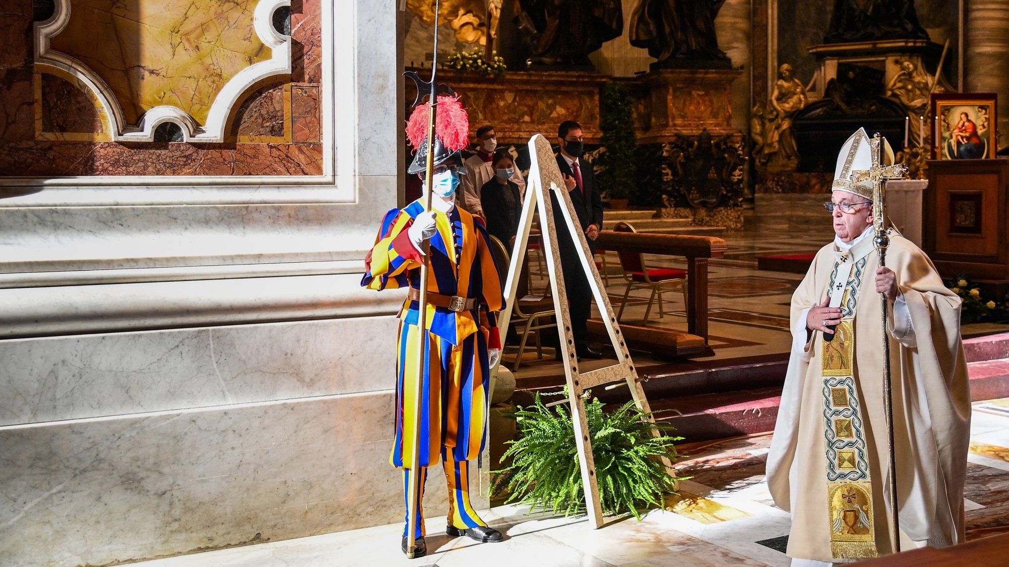 epa08835419 Pope Francis (R) walks by a Swiss Guard wearing a face mask, as he leaves after celebrating a Mass for the feast of Christ the King, as part of World Youth Day at St. Peter's Basilica in The Vatican, 22 November 2020.  EPA/VINCENZO PINTO / POOL
