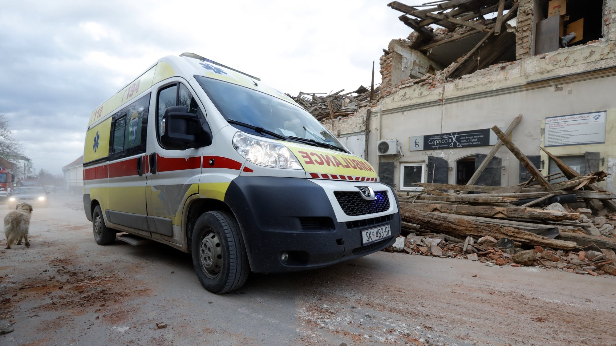 epa08909780 An ambulance drives past buildings damaged in an earthquake in Petrinja, Croatia, 29 December 2020. A 6.4 magnitude earthquake struck around 3km west south west of the town with reports of many injuries and at least one death.  EPA/ANTONIO BAT