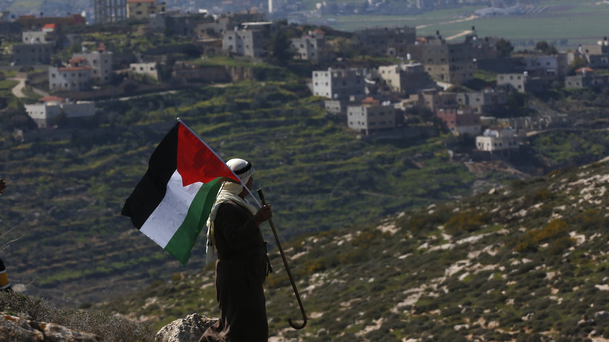 epa09038334 A Palestinian man waves Palestine flag during a demonstration against Israel's settlements in the village of Bet Dajan near the northern West Bank city of Nablus, 26 February 2021.  EPA/ALAA BADARNEH