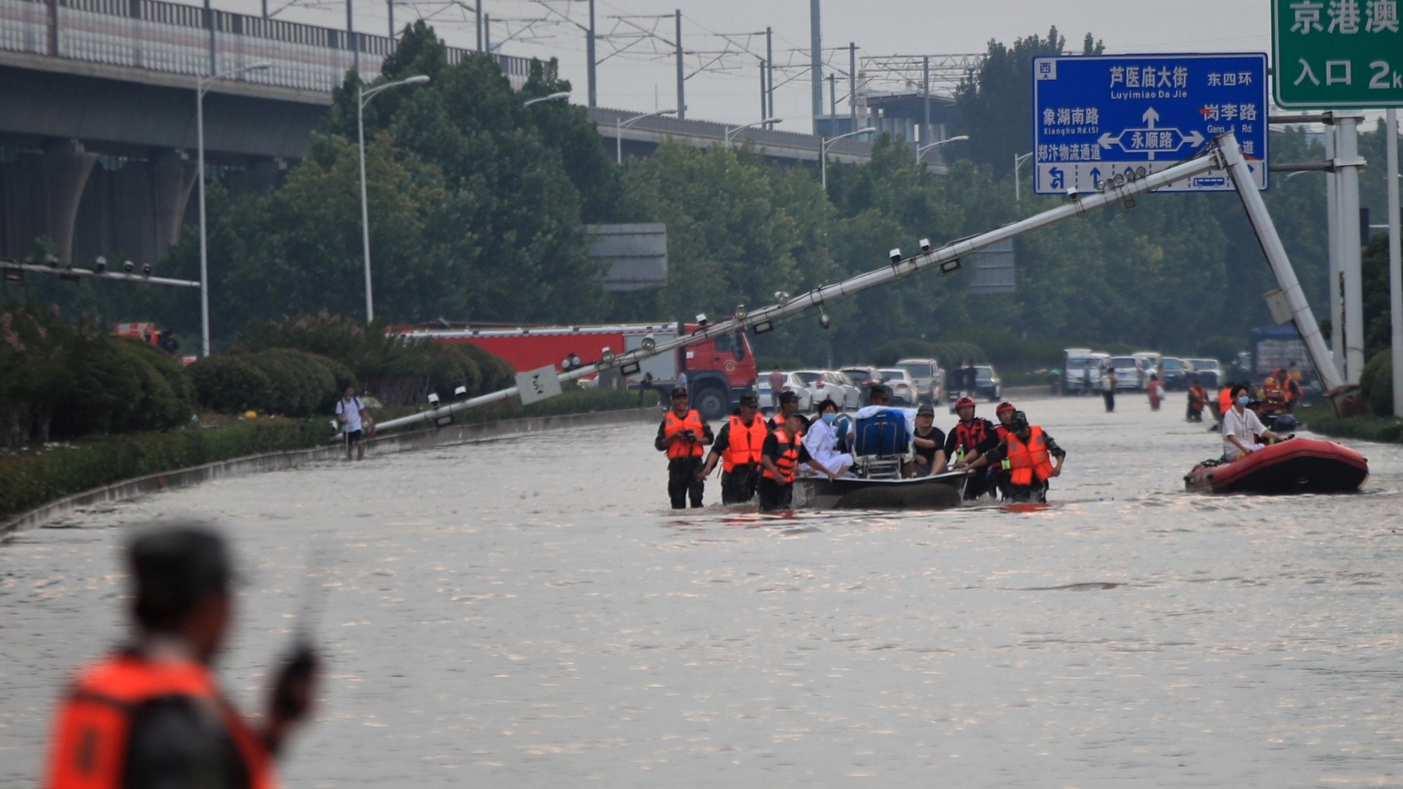 epa09358199 Rescuers evacuate people from a hospital where about 3,000 people were trapped by the flood in Zhengzhou, central China's Henan province, 22 July 2021. Thirty-three people were found dead in the flooding, and eight more are missing.  EPA/STRINGER CHINA OUT