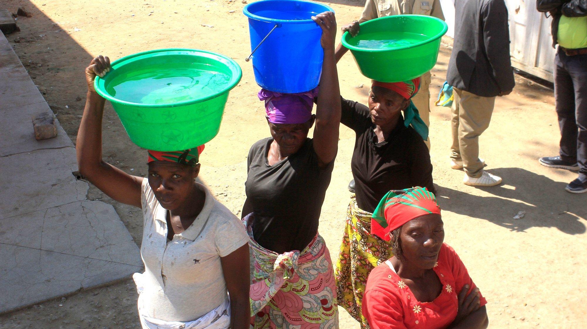 Mulheres transportam na cabeça alguidares com água, no Huambo, Angola, 30 de maio de 2019. AMPE ROGÉRIO/LUSA