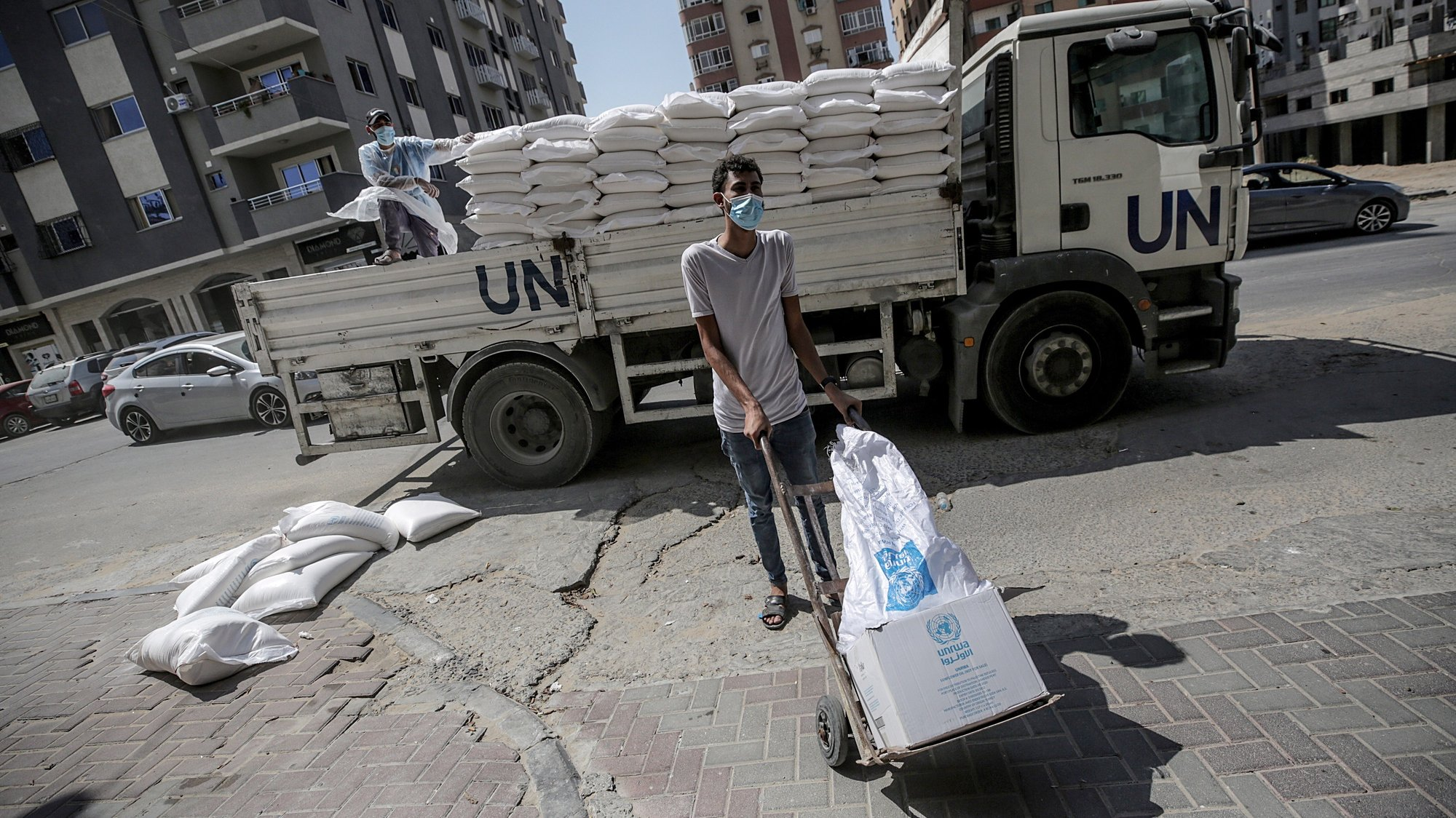 epa08670653 Palestinian workers at the United Nation Relief and Works Agency (UNRWA) wearing protective masks distribute food aid rations for refugee families, in Gaza City, 15 September 2020. UNRWA has resumed food deliveries to thousands of refugee families in the Gaza Strip amid the ongoing coronavirus COVID-19 pandemic.The Gaza Strip is under a nationwide lockdown from 25 August.  EPA/MOHAMMED SABER