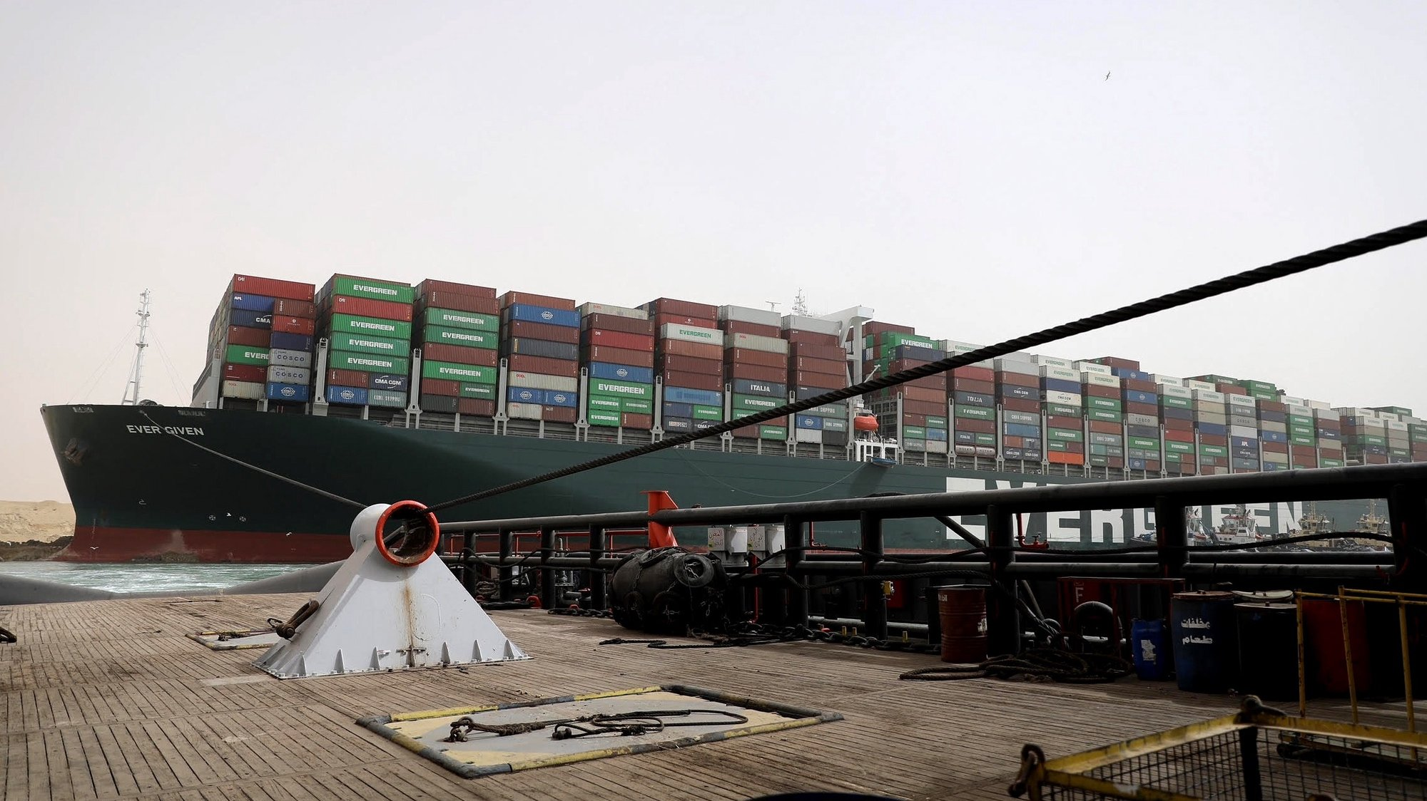 """epa09095658 A handout photo made available by the Suez Canal Authority, shows ropes  from an Egyptian tugboat pulling the Ever Green container ship in the Suez Canal, Egypt, 25 March 2021. The Ever Given, a large container ship ran aground in the Suez Canal on 23 March, blocking passage of other ships and causing a traffic jam for cargo vessels.  The head of the Suez Canal Authority announced on 25 March that """"the navigation through the Suez Canal is  temporarily suspended"""" until the floatation of  the Ever Given is completeted. Its floatation is being carried out by 8 large tugboats that are towing and pushing the grounding vessel.  EPA/SSUEZ CANAL AUTHORITY/HANDOUT  HANDOUT EDITORIAL USE ONLY/NO SALES HANDOUT EDITORIAL USE ONLY/NO SALES"""