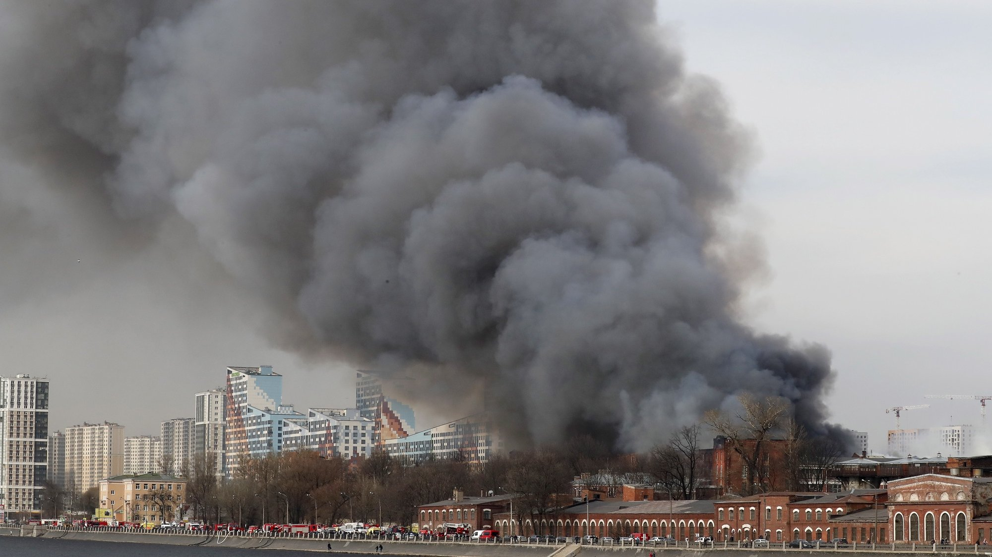 epa09130981 Smoke and fire rise over the building of the factory 'Nevskaya manufactory' located near the Oktyabrskaya embankment of the Neva in St. Petersburg, Russia, 12 April 2021. Some 300 firefighters and 60 pieces of equipment and a helicopter are taking part in extinguishing the fire. One firefighter was killed when extinguishing the fire.  EPA/ANATOLY MALTSEV